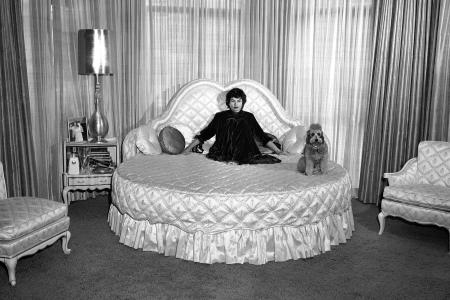 "Eden Hartford Marx, wife of Groucho, in her white and gold bedroom and bathroom in Beverly Hills, March 1958. The white and gold motif is carried out in both these room, including bed and other furnishings and the equipment in the bathroom. Pooch's name is DeSoto,"" a family pet. ()"