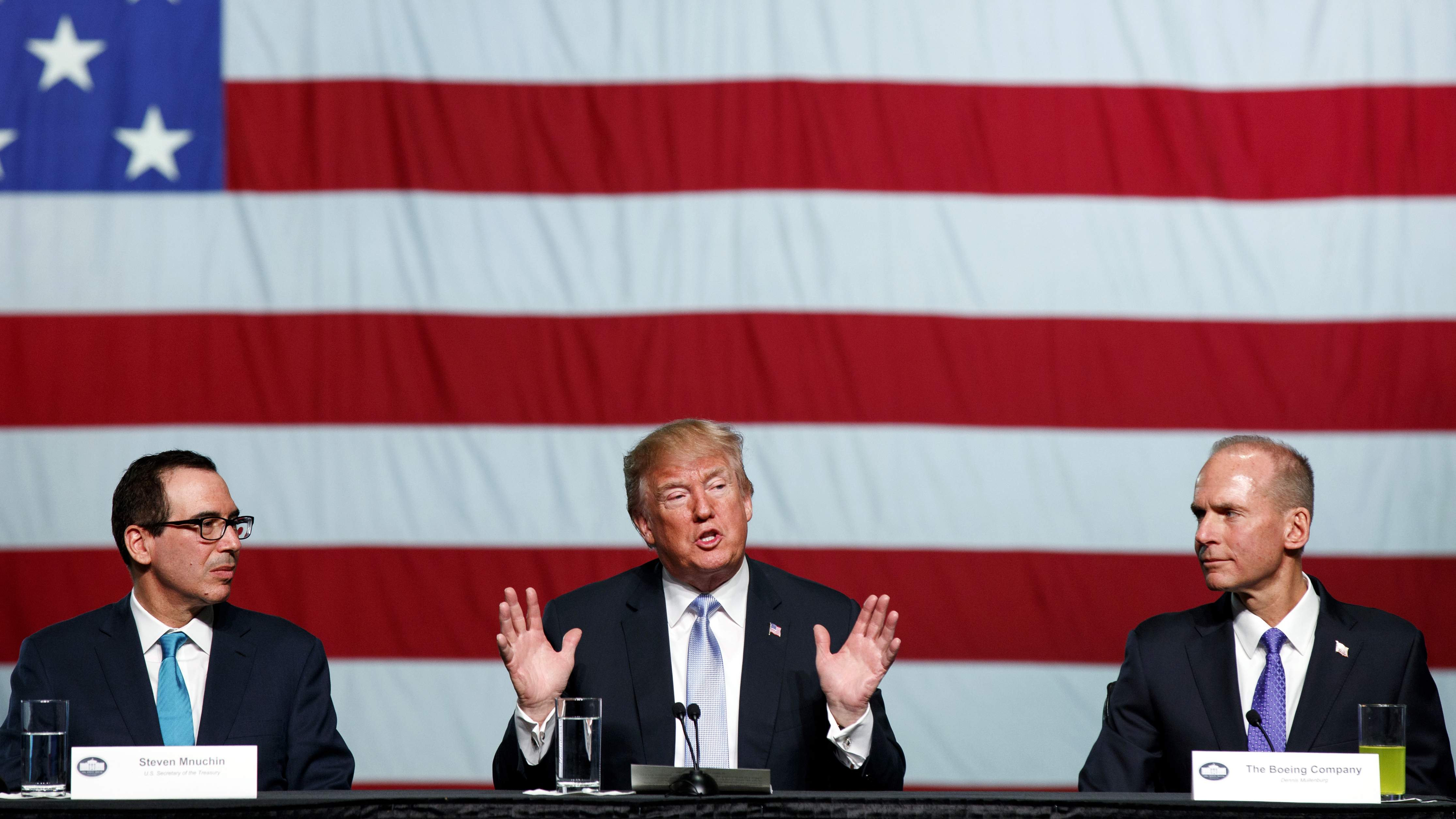 Treasury Secretary Steve Mnuchin, left, and Boeing CEO Dennis Muilenburg, right, listens as President Donald Trump speaks during a roundtable discussion on tax policy at the Boeing Company, Wednesday, March 14, 2018, in St. Louis.