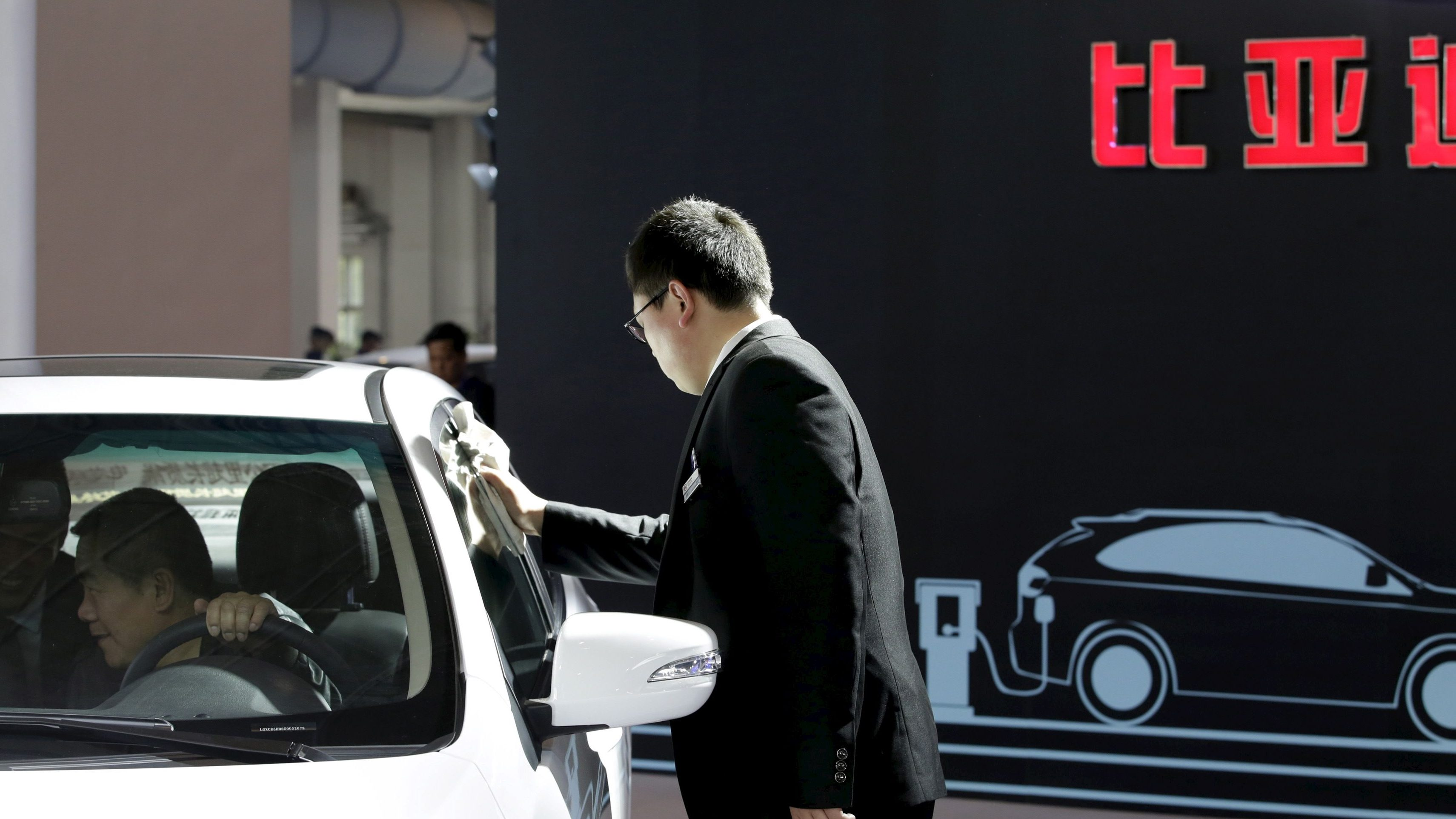A staff member cleans a BYD electric car during the Auto China 2016 in Beijing, China, April 25, 2016.