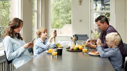 Shot of a family of four distracted by their cellphones while eating breakfast together
