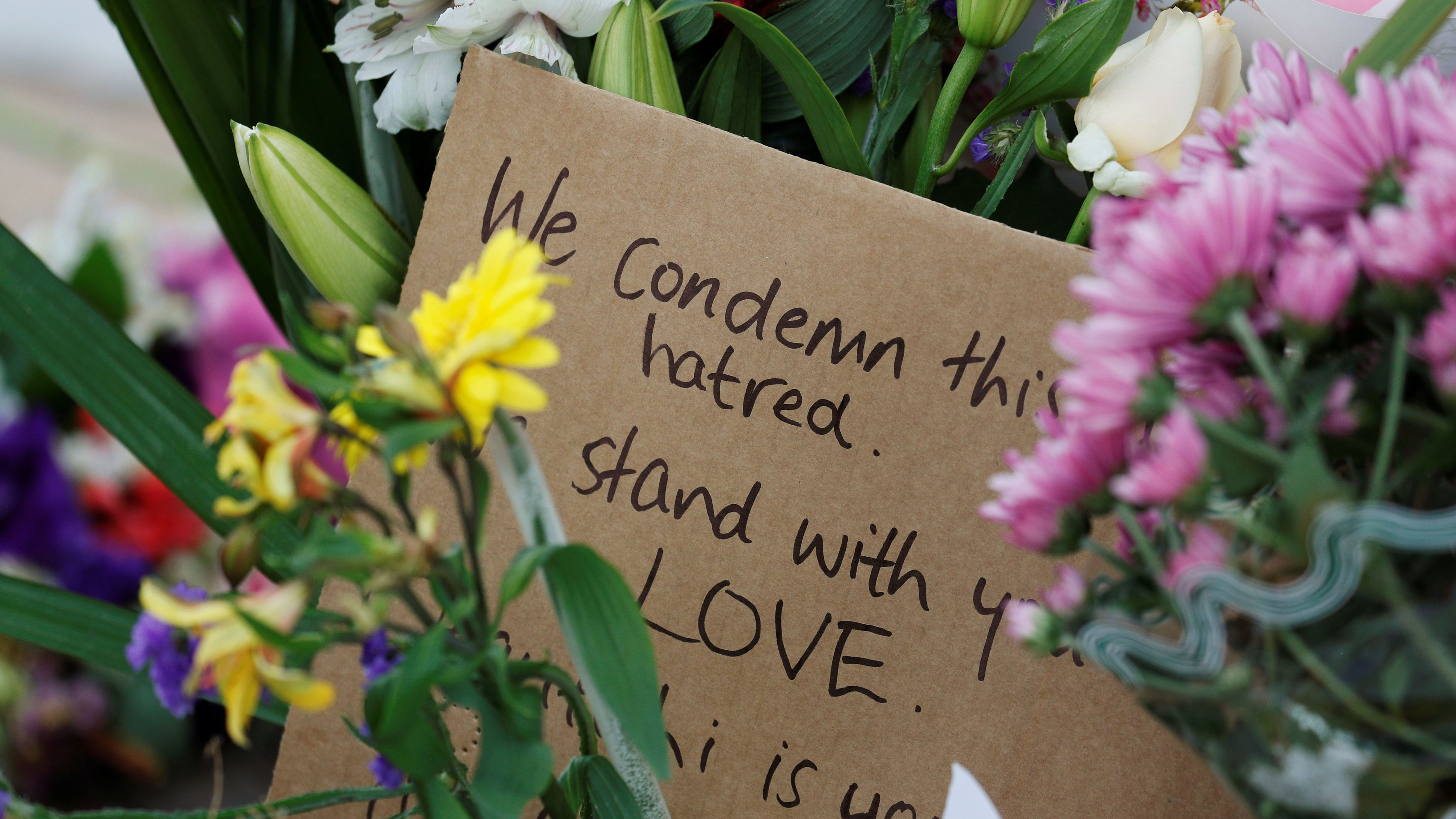 Flowers and signs are seen at a memorial as a tribute to victims of the mosque attacks, near a police line outside Masjid Al Noor in Christchurch, New Zealand,