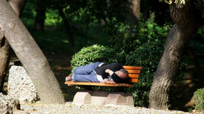 Man takes advantage of autumn sun and naps on a bench at a park in Istanbul