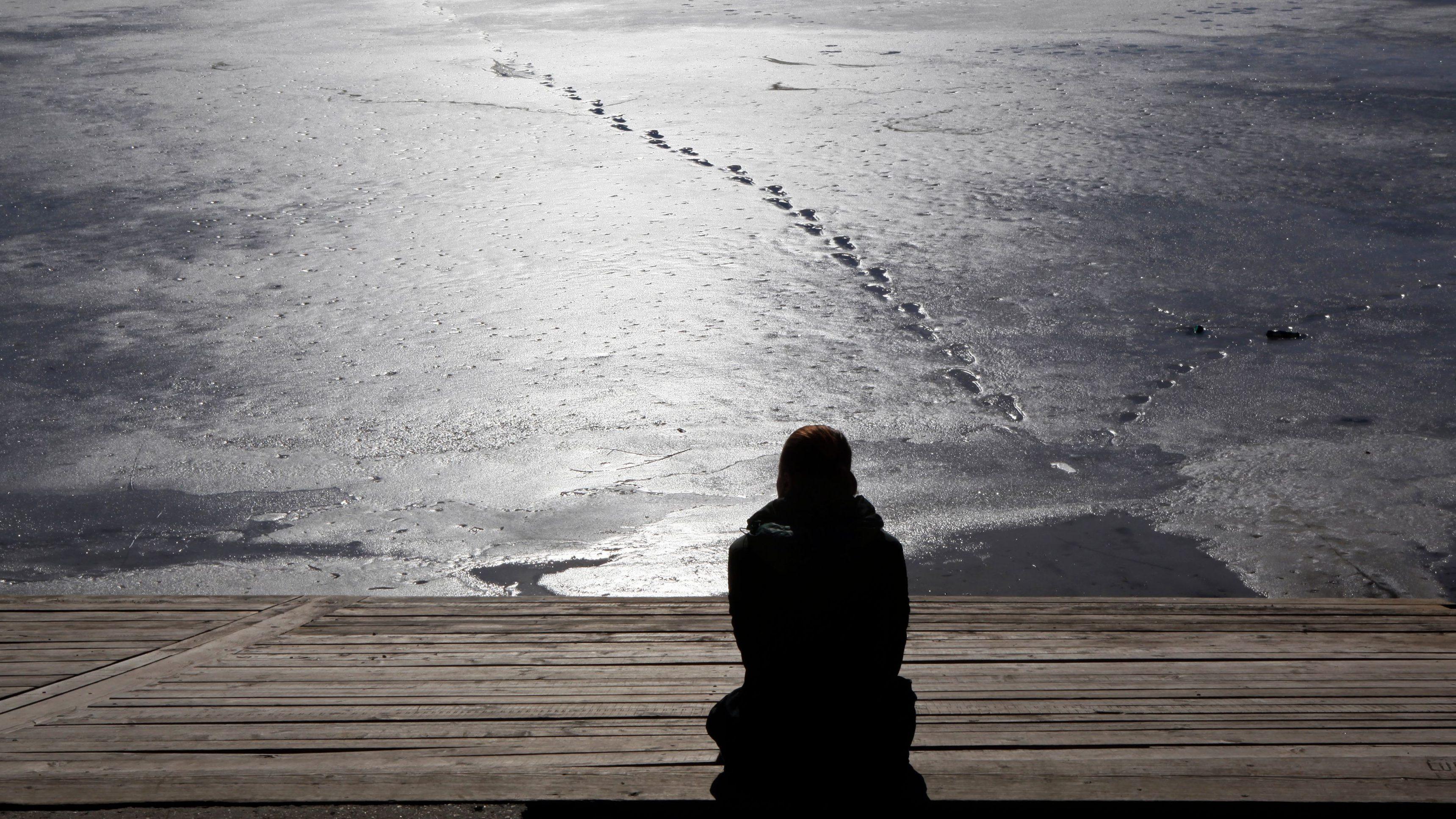 A woman enjoys the sun on the shore of a frozen lake.