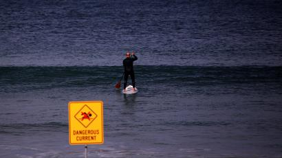 A man stands on a paddleboard behind a warning sign on a Spring day at Sydney's Manly Beach