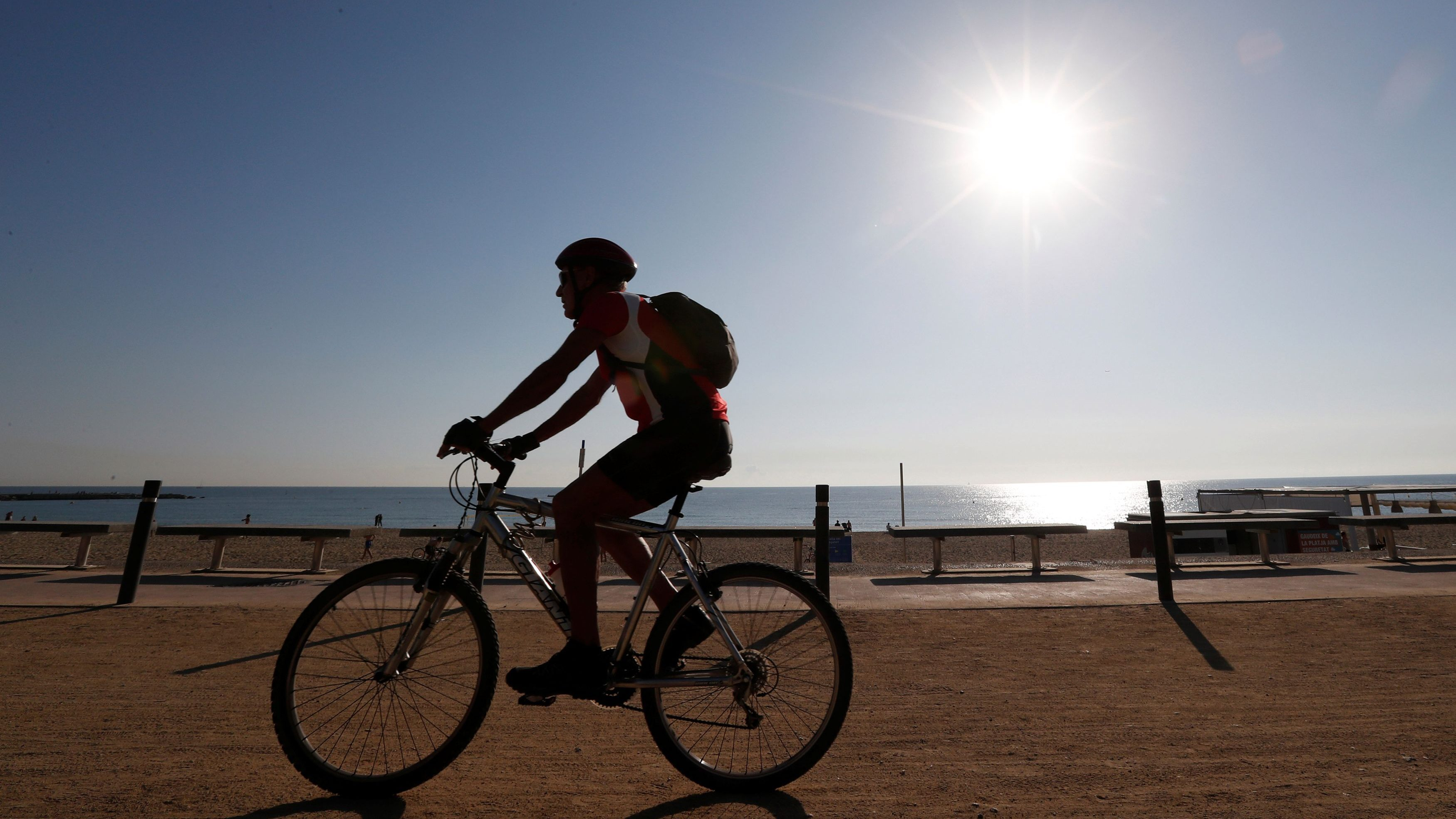 A man rides his bicycle on a hot day in Barceloneta beach in Barcelona
