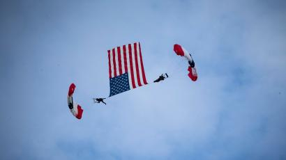 Skydivers fly an American flag