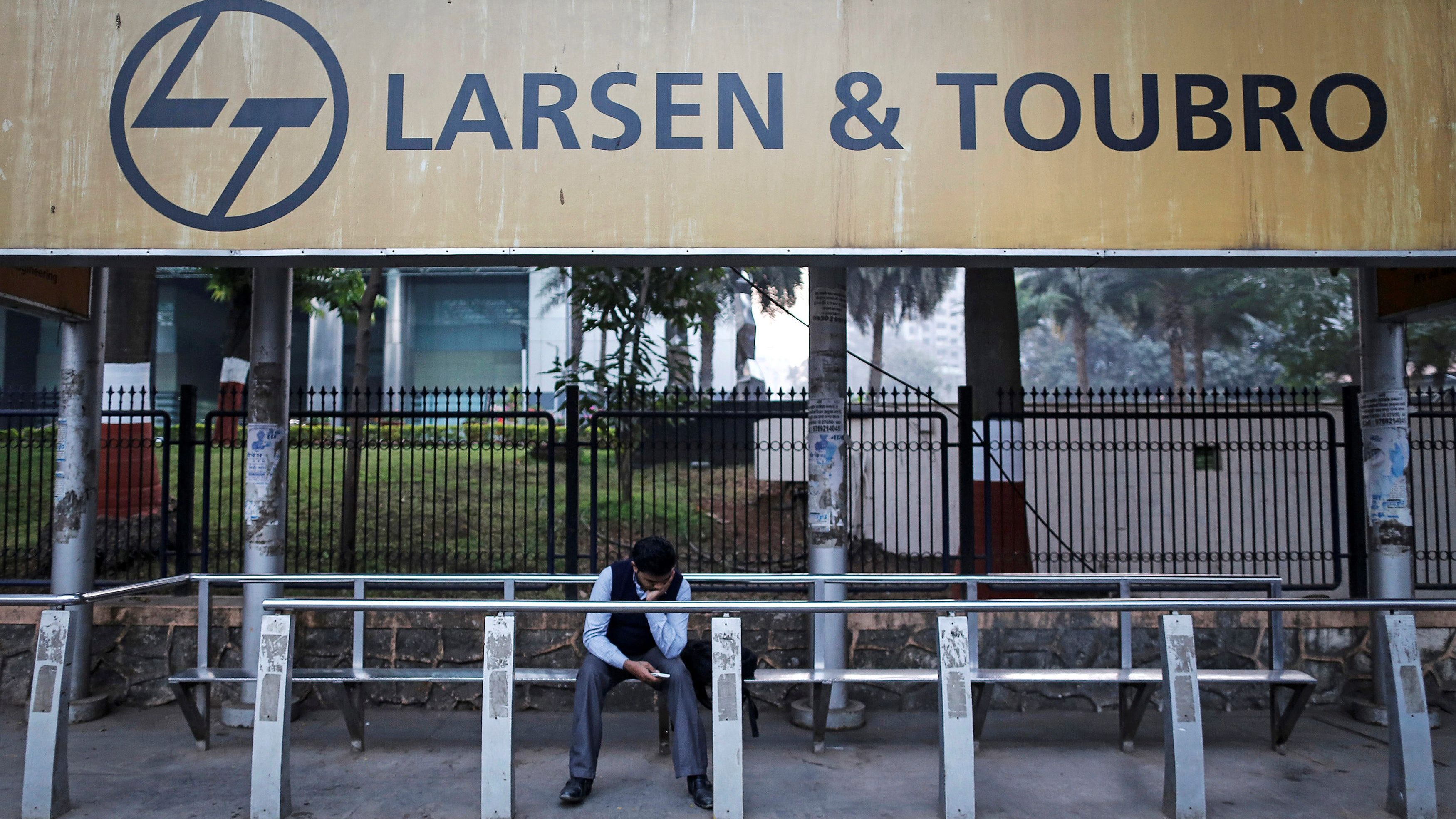 FILE PHOTO: A man waits at a bus-stop with an advertisement of Larsen & Toubro outside the company's manufacturing unit in Mumbai