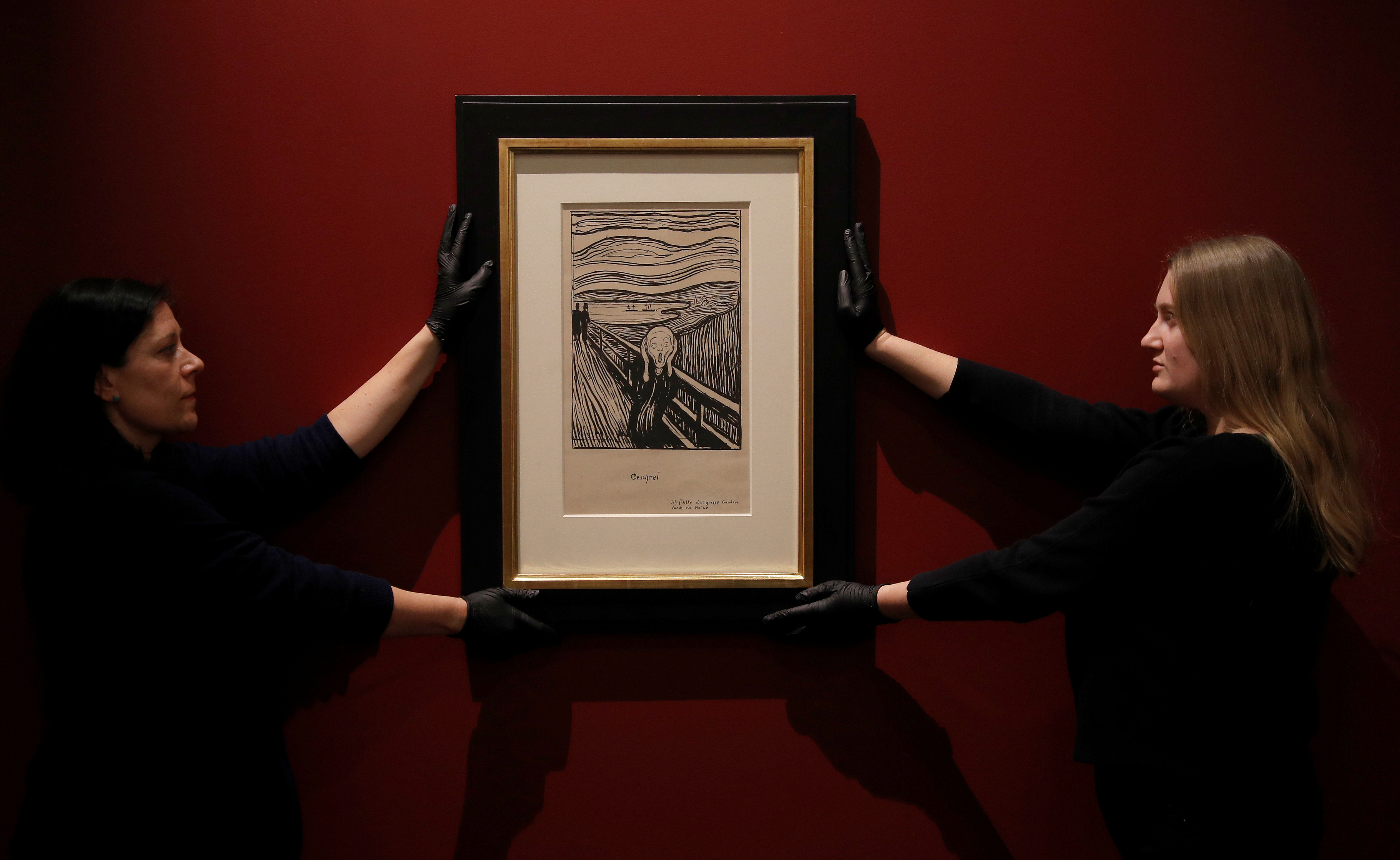 """Staff-members pose for a photograph as they hang a lithograph of The Scream by Edvard Munch ahead of the exhibition """"Edvard Munch: love and angst"""", soon to be on display at the British Museum in London, Britain, March 20, 2019."""