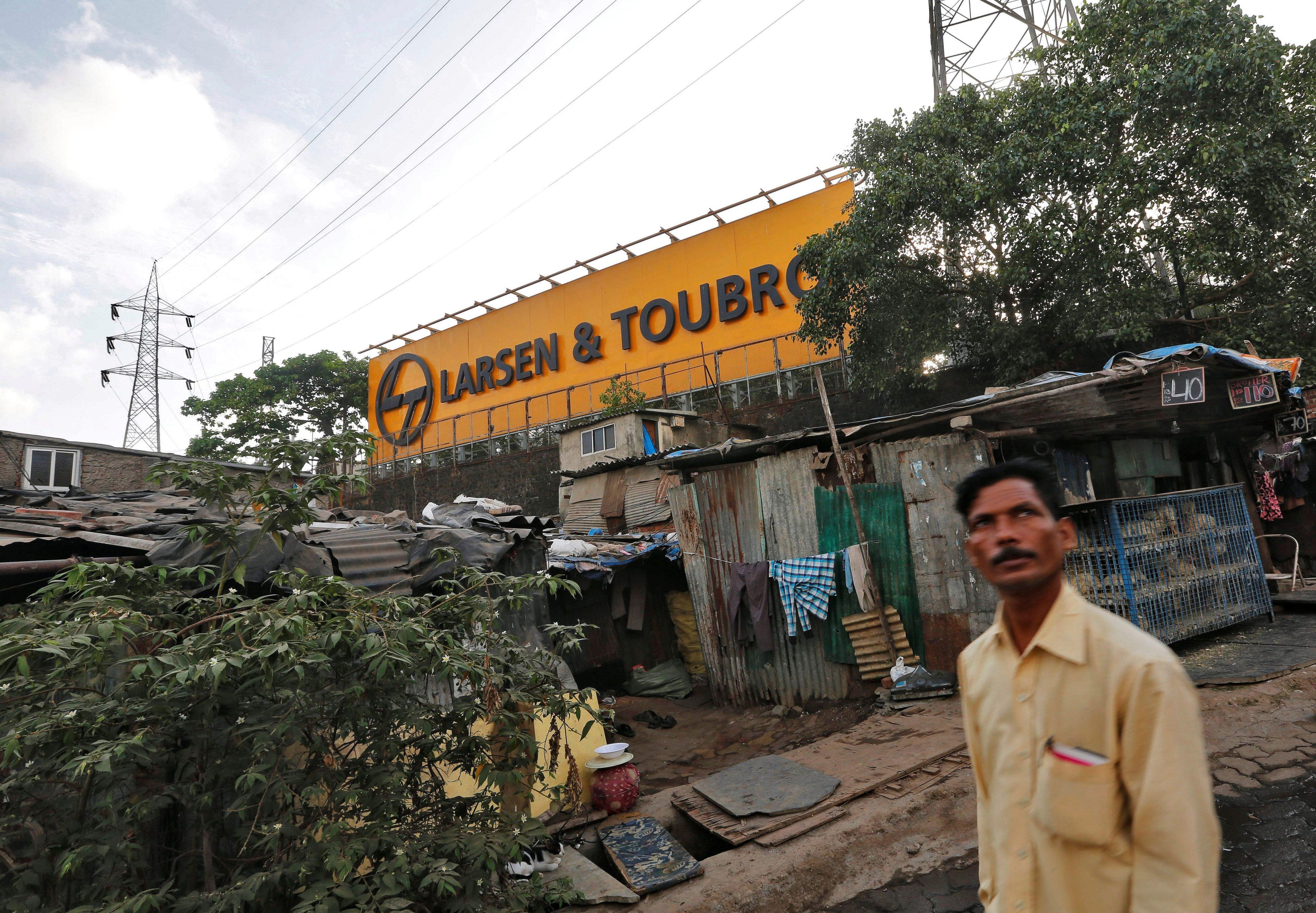 A man walks through a slum outside the L&T factory in Mumbai