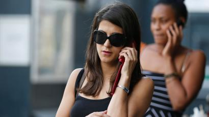 Women use their mobile phones in central London.