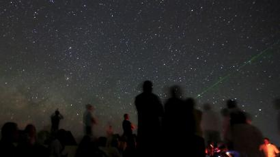 Campers look up at stars in the night sky in the White Desert north of the Farafra Oasis southwest of Cairo