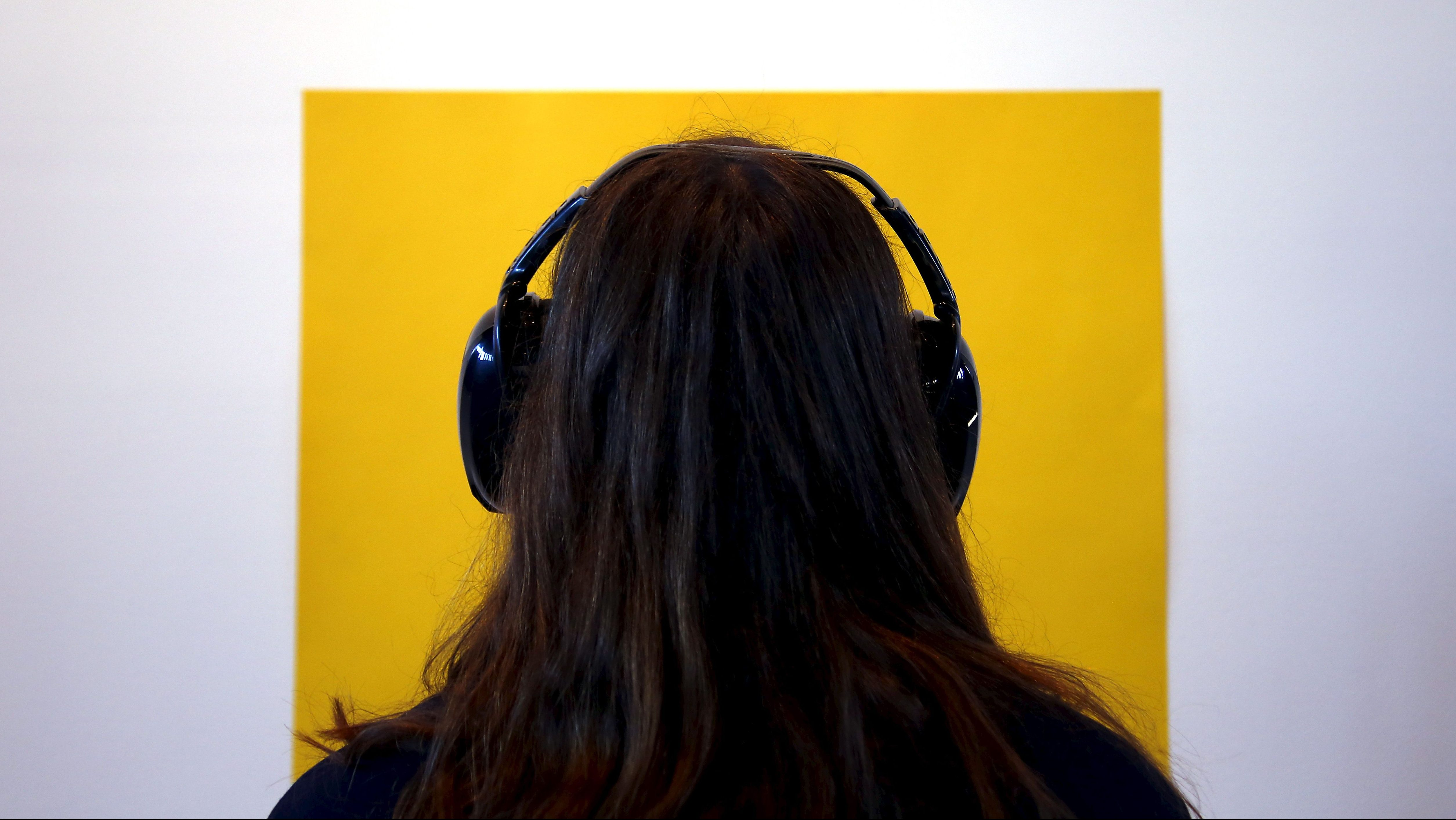 """A visitor wearing noise-cancelling headphones as she tours the latest project by performance artist Marina Abramovic titled """"Marina Abramovic: In Residence"""" on display as part of a public art project in Sydney"""