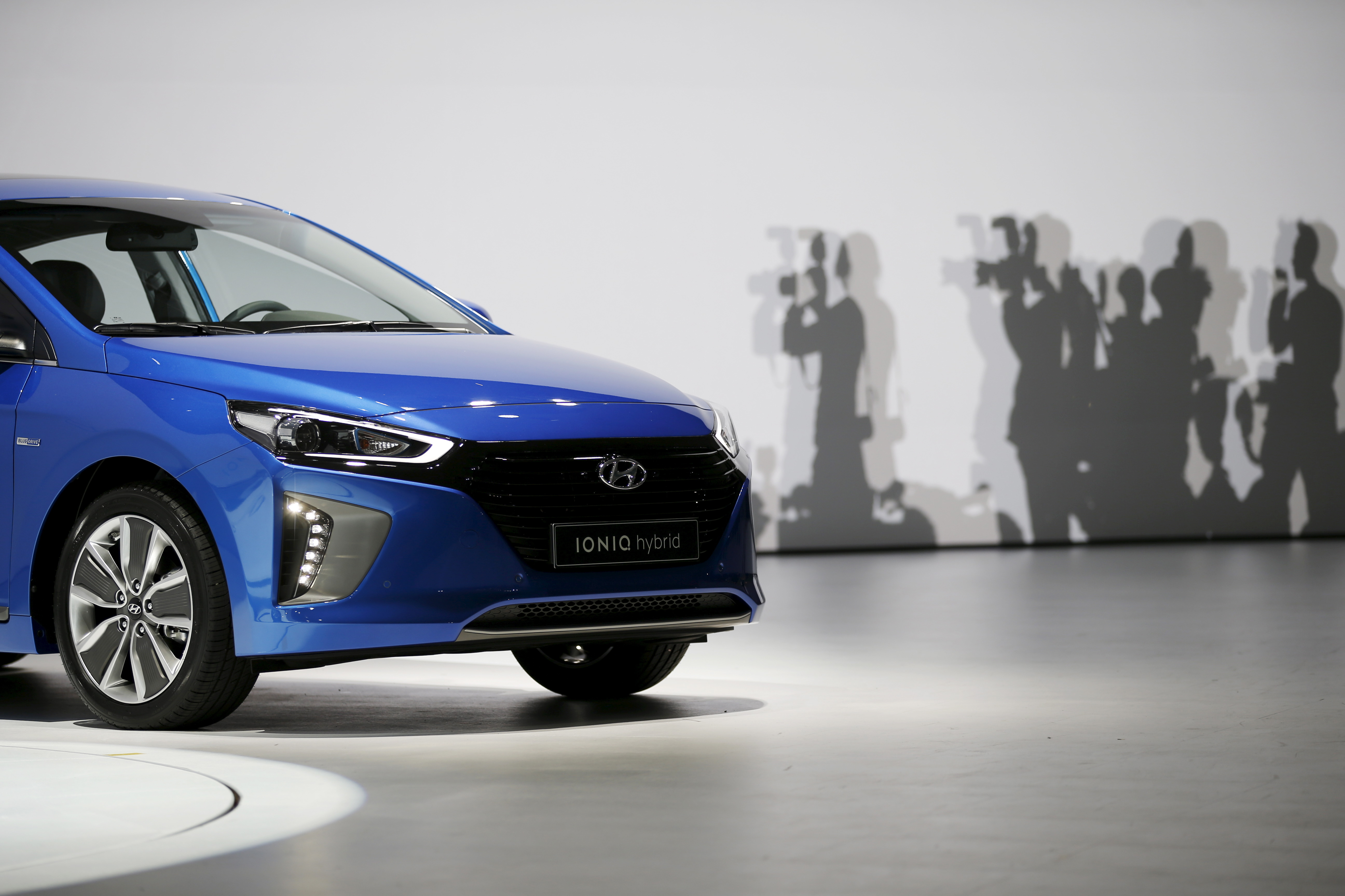 Journalists take photographs of Hyundai Motor's first hybrid car IONIQ during its unveiling ceremony in Seoul