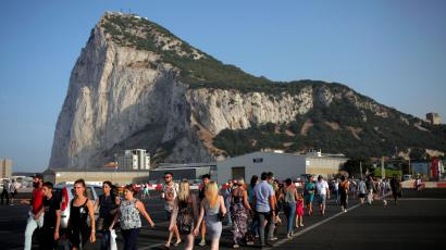Pedestrians cross the tarmac at Gibraltar International Airport in front of the Rock near the border with Spain in the British overseas territory of Gibraltar