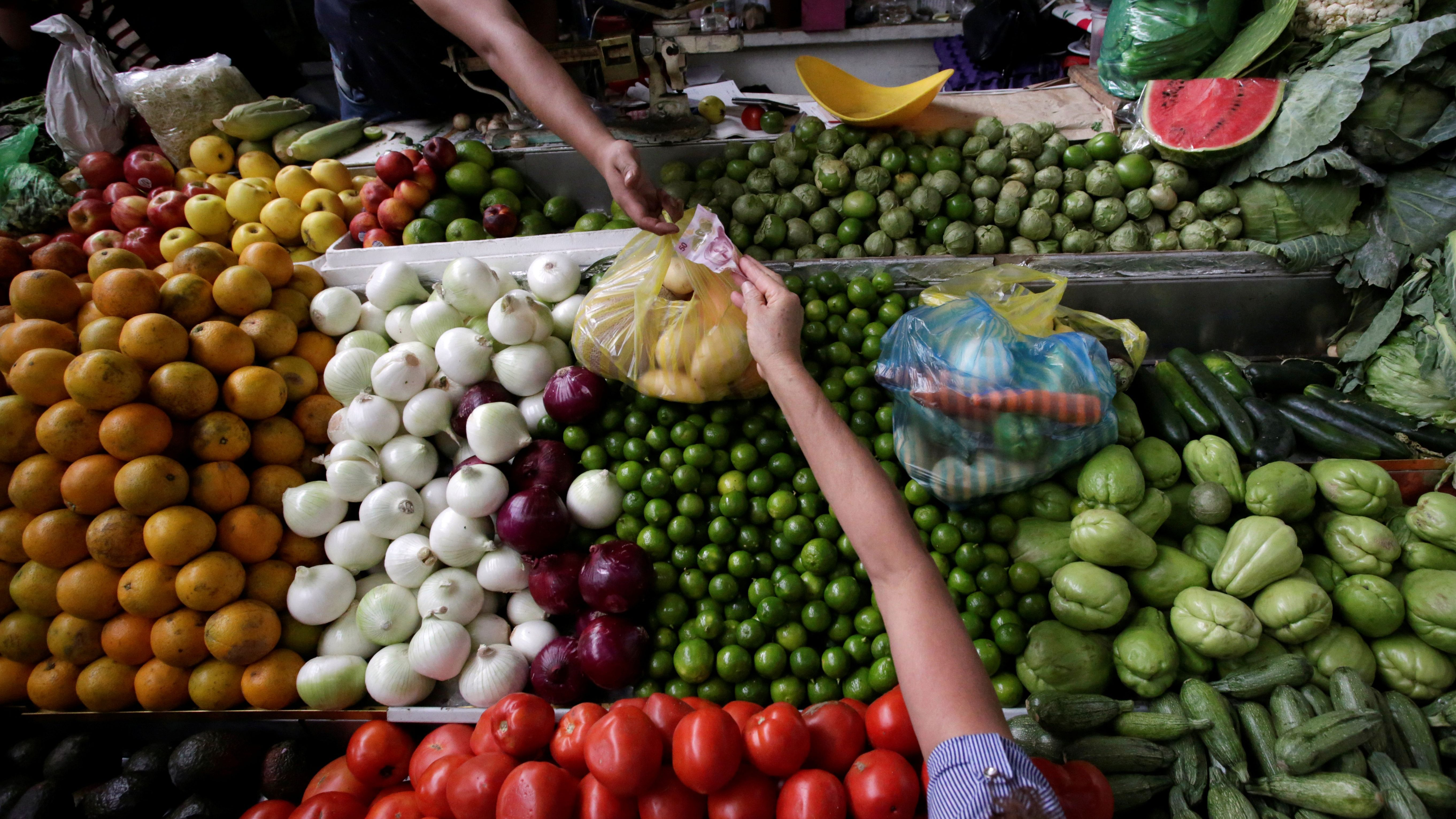 A woman buys vegetables at a market stall in Mexico City