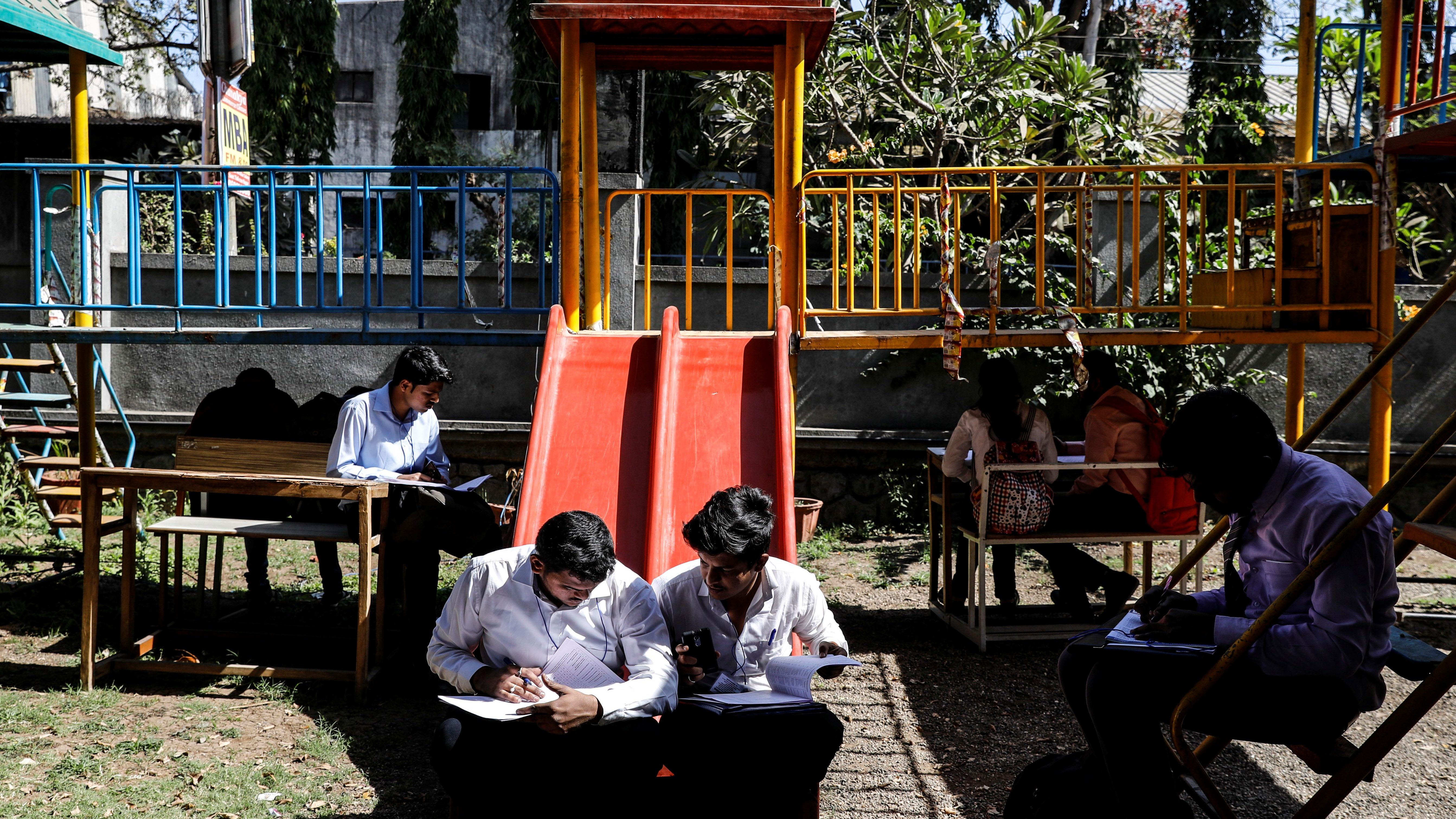 Job seekers fill up their forms while sitting on swings before lining up for interviews at a job fair in Chinchwad