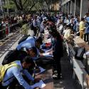 Job seekers fill up forms as others line up for registration during a job fair in Chinchwad