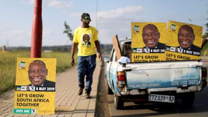 Musa Masina looks at election posters with the face of ANC president Cyril Ramaphosa, before hanging them on street poles in Soweto, South Africa, March 12, 2019.