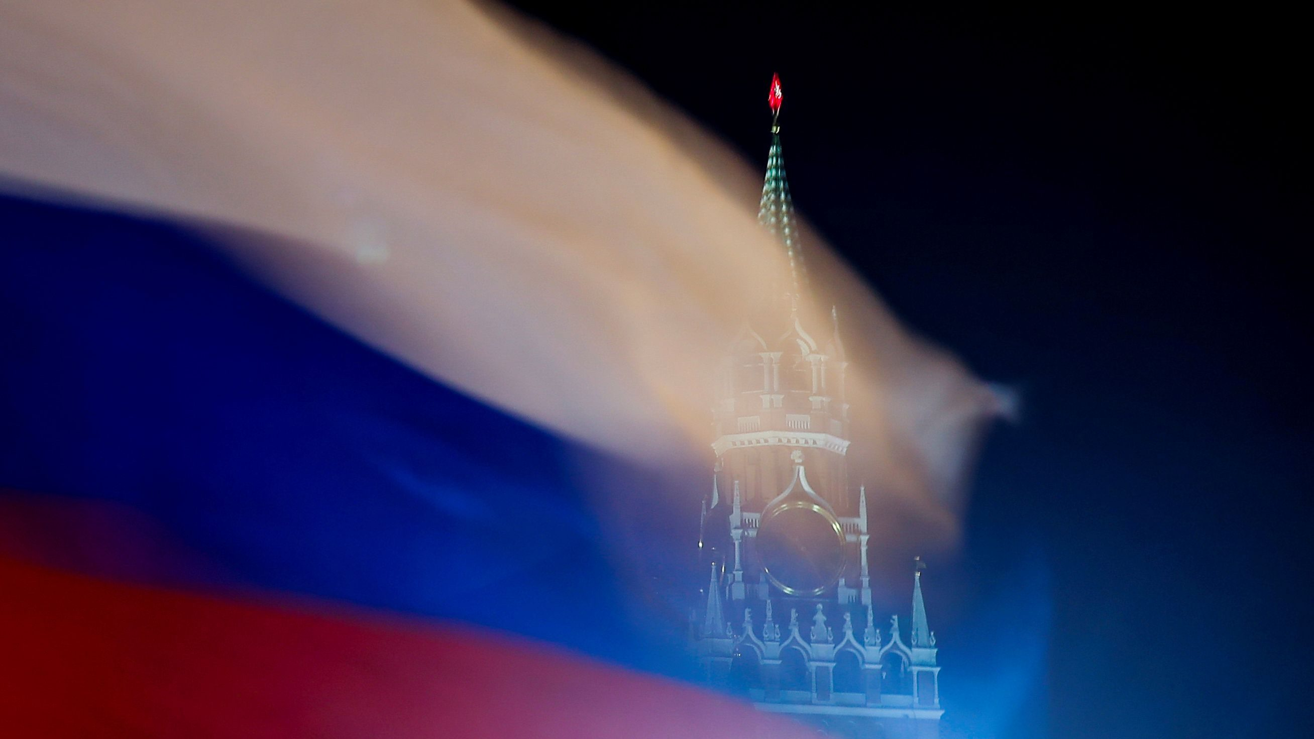A Russian flag flies with the Spasskaya tower of Moscow's Kremlin in the background