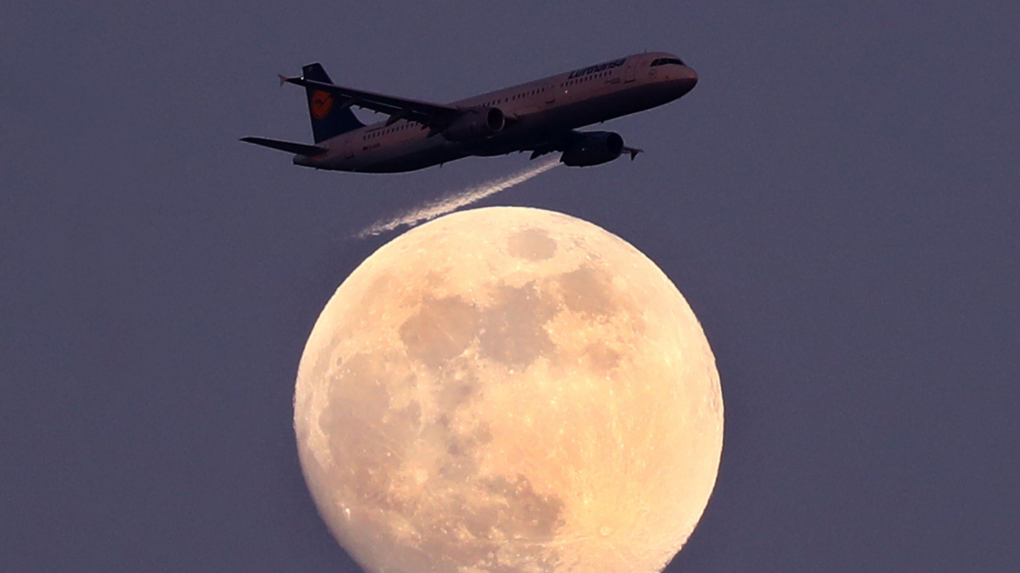 An airplane of German air carrier Lufthansa passes the moon over Frankfurt, Germany, April 9, 2017.