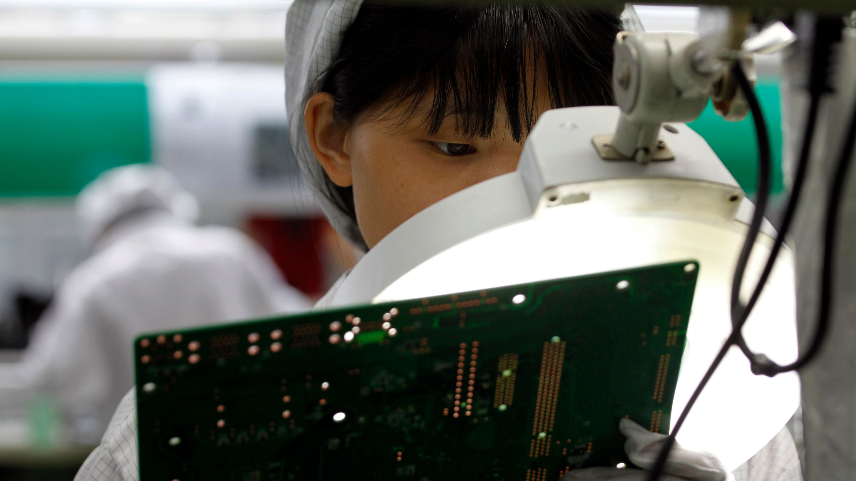 A worker examines a circuit board inside a Foxconn factory in the township of Longhua in the southern Guangdong province May 26, 2010. A spate of nine employee deaths at global contract electronics manufacturer Foxconn, Apple's main supplier of iPhones, has cast a spotlight on some of the harsher aspects of blue-collar life on the Chinese factory floor.