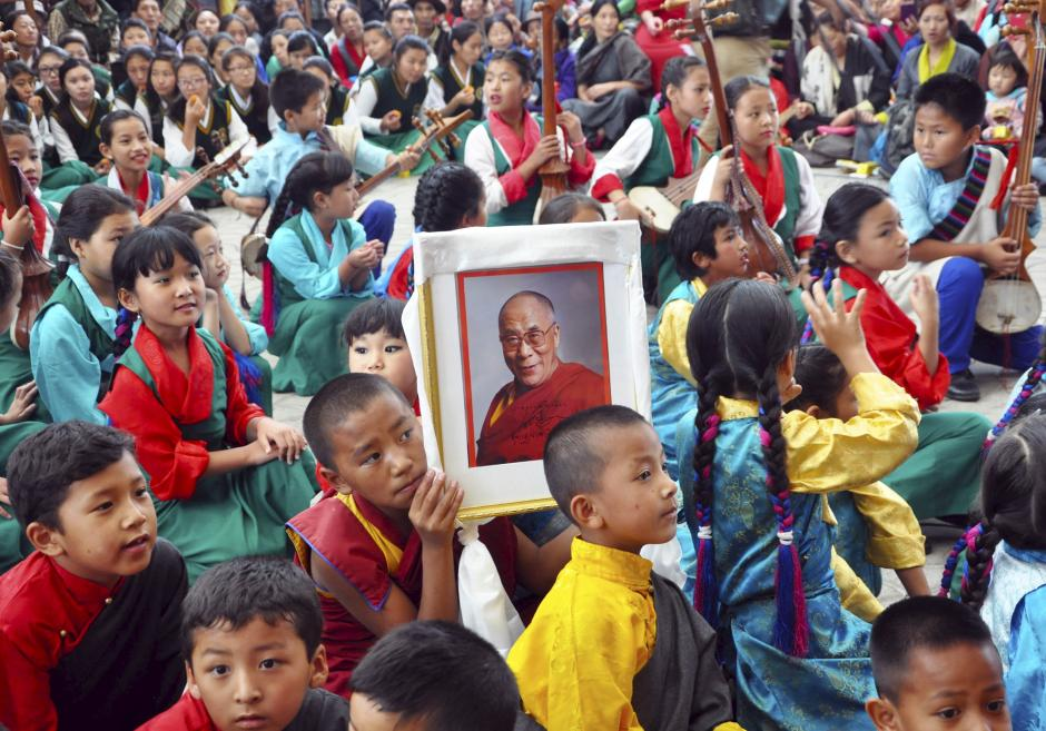 A young Tibetan monk holds a portrait