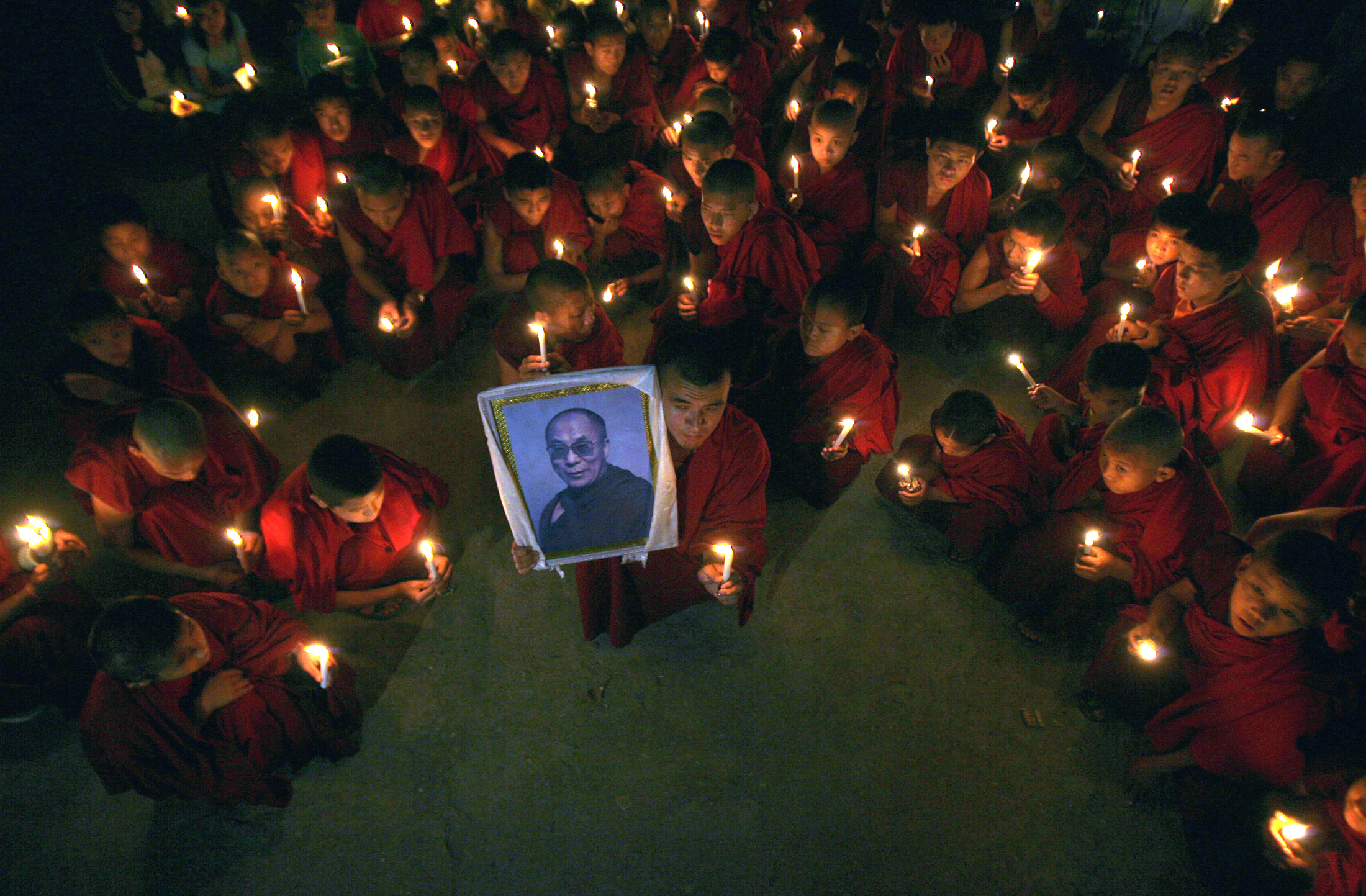 Tibetan monks take part in a candle light rally