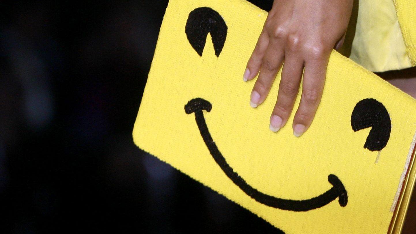 A model carries a smiling emoji purse