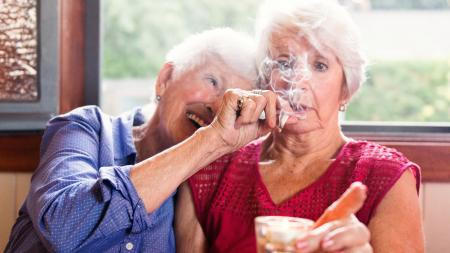Two senior girlfriends 83 years old smoke medicinal marijuana together. One of them shows the other how to do. The old lady is surprise and making a face. They have hair and wear casual clothes. The recreational marijuana become legal in Canada next autumn. Photo was taken in Quebec Canada.