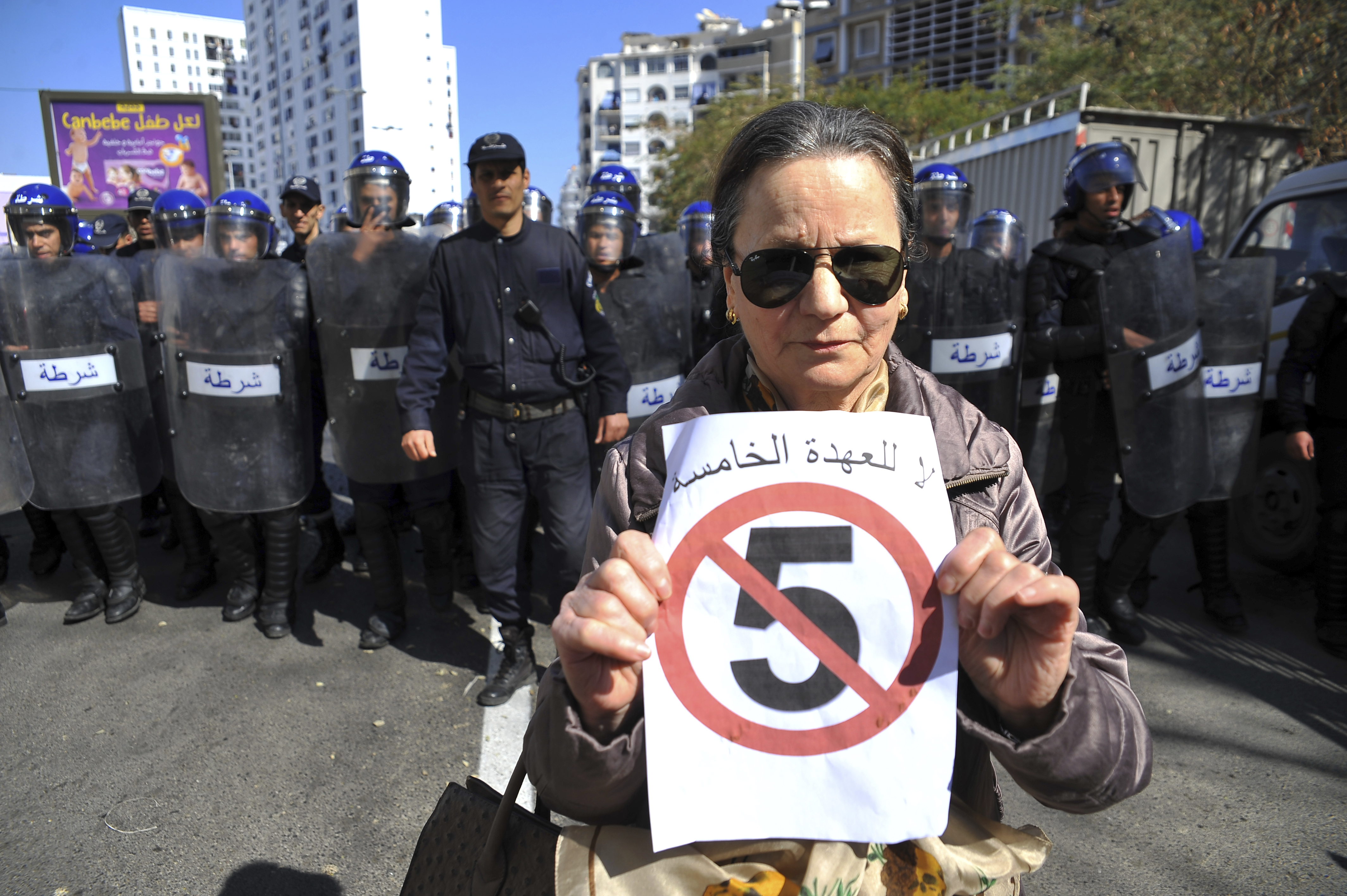 "A woman poses with a sign reading ""No to a 5th turn"" in front of a line of police officers as she demonstrates with others to denounce President Abdelaziz Bouteflika's bid for a fifth term, Friday, March 1, 2019. Tens of thousands of protesters marched through Algeria's capital Friday against ailing President Abdelaziz Bouteflika's bid for a fifth term, surging past a barricade and defying repeated volleys of tear gas fired by police during the tense demonstration."