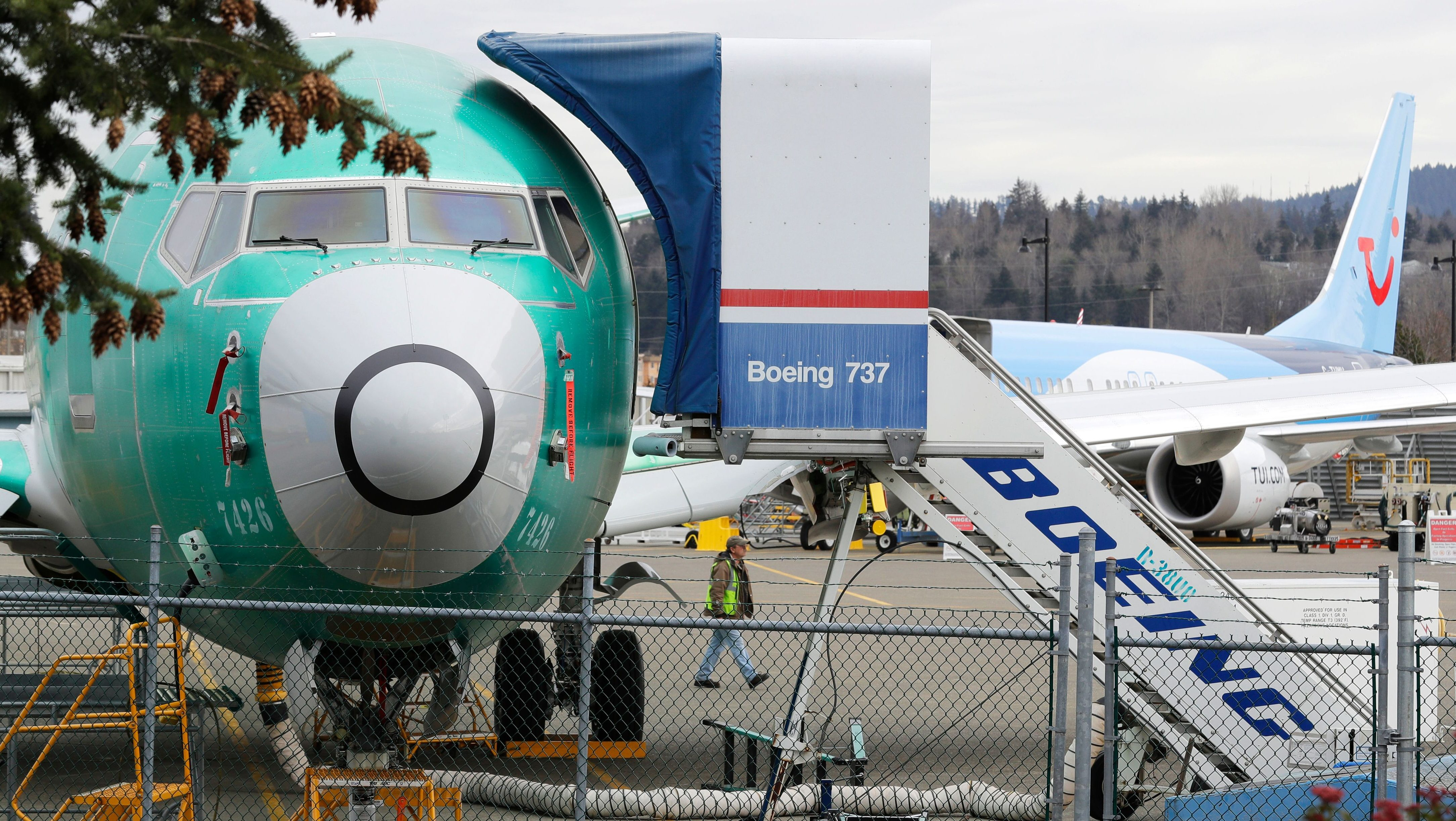 A worker walks near a Boeing 737 MAX 8 being built for for Shanghai Airlines at Boeing Co.'s Renton Assembly Plant, Monday, March 11, 2019, in Renton, Wash. Airlines in several countries grounded the same model jetliner Monday following Sunday's crash of an Ethiopian Airlines Boeing 737 Max 8, the second devastating crash of one of the planes in five months.