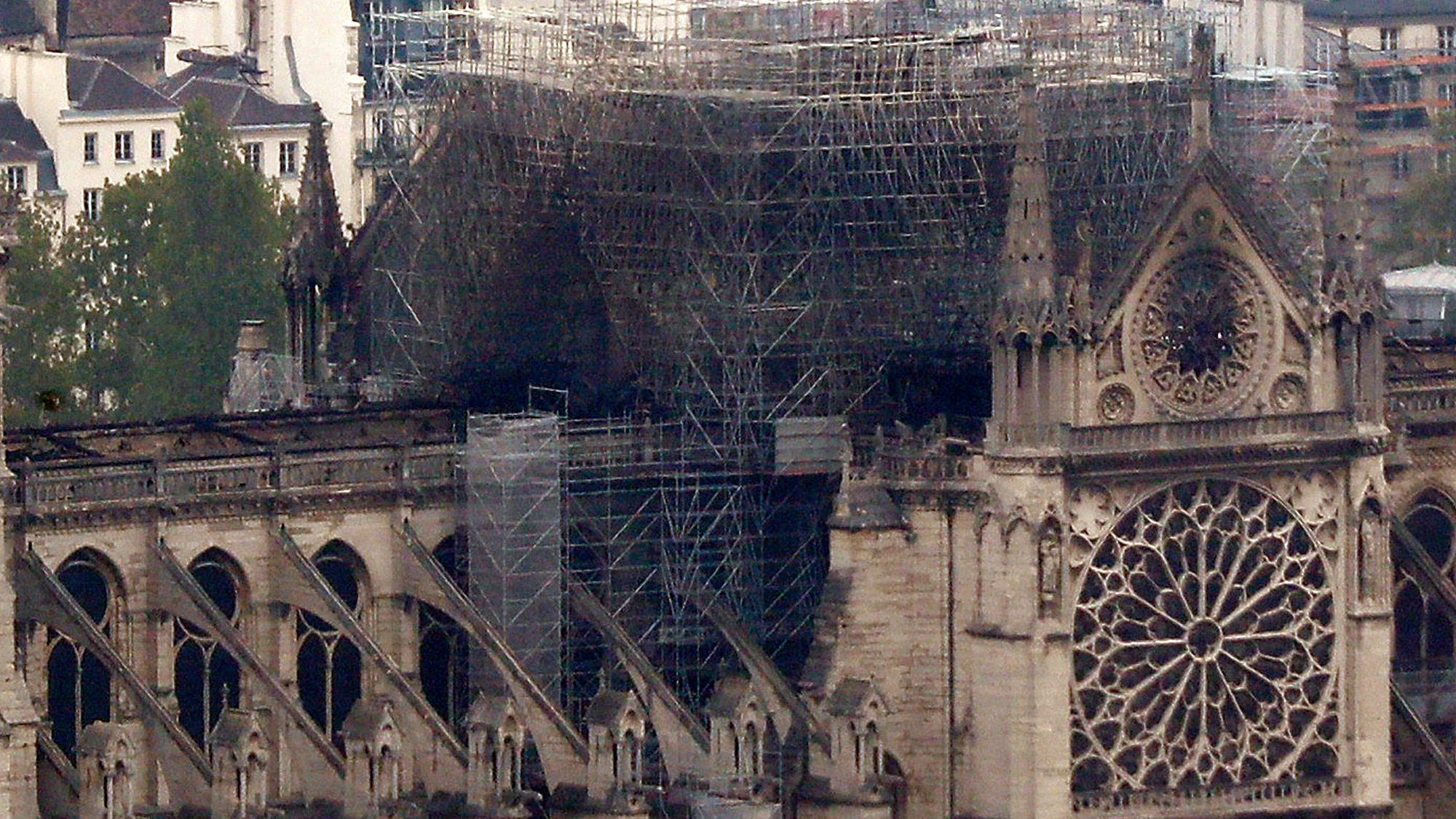 Notre Dame cathedral is pictured from the top of the Montparnasse tower, Tuesday April 16, 2019 in Paris. Firefighters declared success Tuesday morning in an over 12-hour battle to extinguish an inferno engulfing Paris' iconic Notre Dame cathedral that claimed its spire and roof, but spared its bell towers. (AP Photo/Thibault Camus)