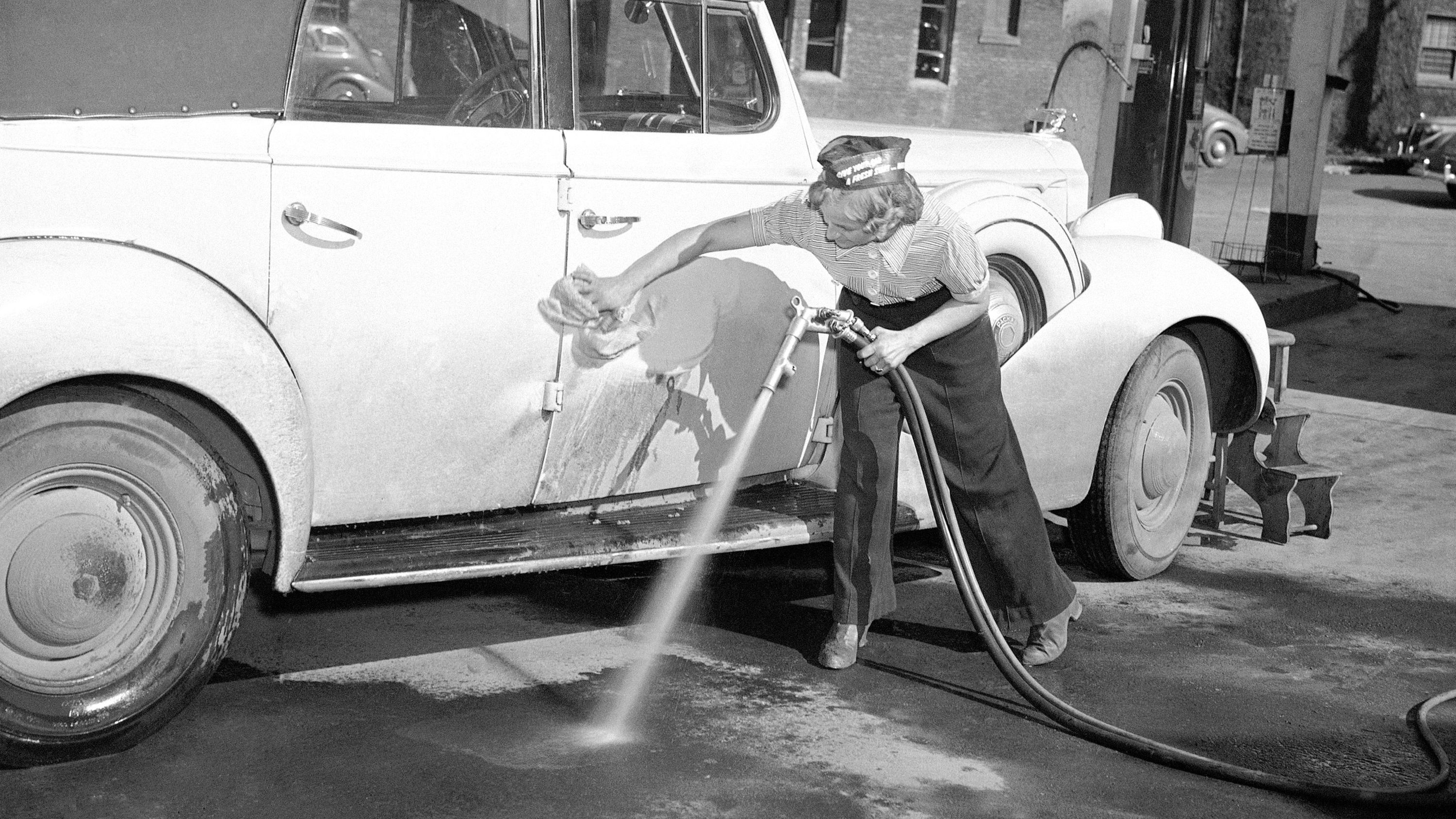 Labor shortage in Portland has caused women to take over certain jobs previously held by men. Gertrude Rutter is now a car-washer at a local gasoline station in Portland, Oregon, April 3, 1942. (AP Photo)