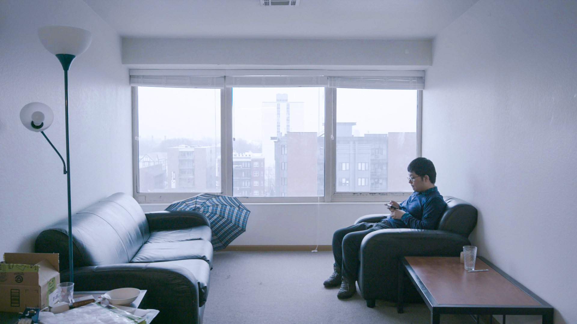 A Chinese student sitting in his livingroom