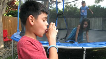 In this April 4, 2017 photo, Javier Sua demonstrates how he uses an inhaler at his home in Fresno, Calif. He uses it to combat asthma, made worse by air pollution in the San Joaquin Valley. On some days, his mother keeps him inside, when he would rather be rough-housing on the backyard trampoline, but the risks are too high. Hundreds of people each year in the San Joaquin Valley die premature deaths from poor air quality.