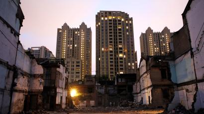 Large apartment buildings behind dilapidated houses.