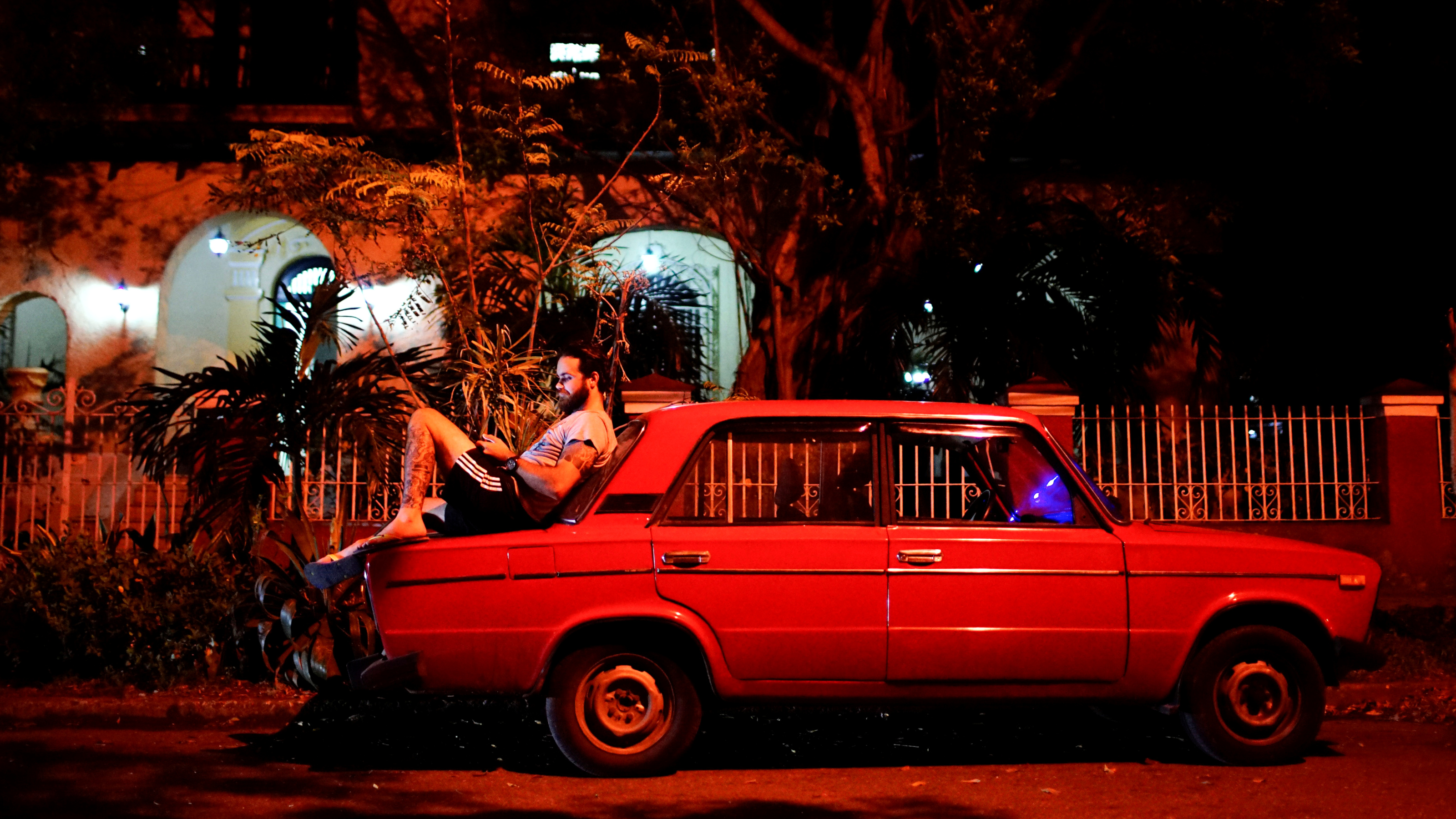 Tourist guide Daniel Hernandez, 26, sits on his Russian-made car as he speaks to his girlfriend who lives in Britain, at an internet hotspot in Havana, Cuba, September 24, 2017.
