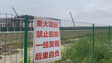 A sign on the fence of the Gigafactory said no aerial photography.