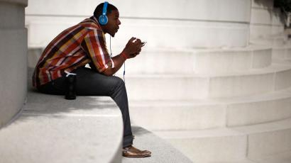 A man with Beats headphones listens to music on an iPhone