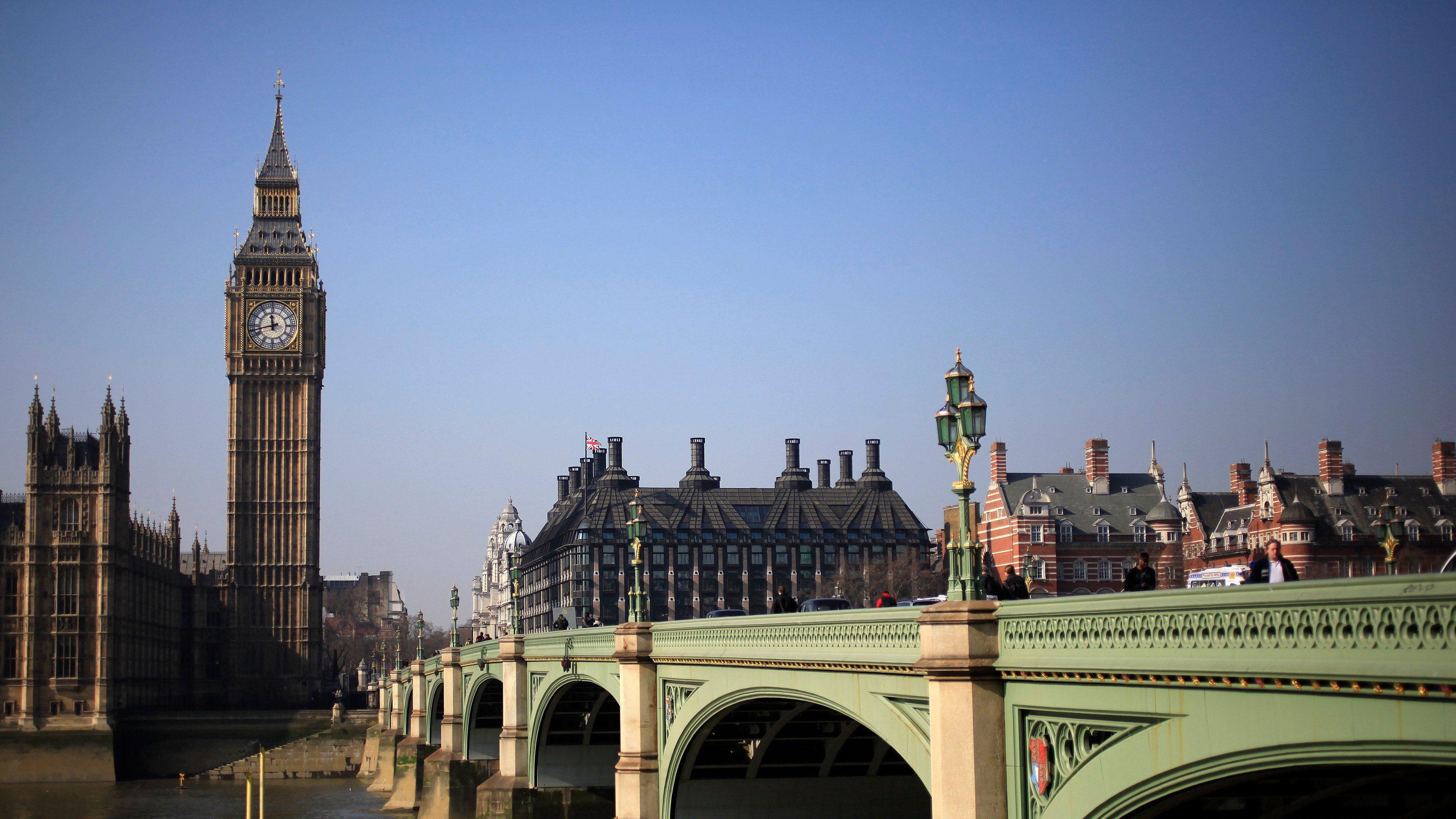 Pedestrians walk across Westminster Bridge in front of the Big Ben Clock Tower