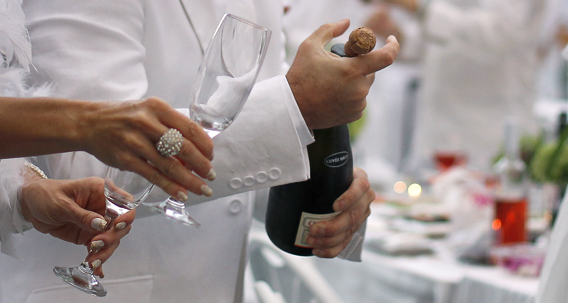 A man corks a champagne bottle as he participates in the White Dinner in Quebec City August 18, 2011. Guests are required to be dressed in white and bring their own food, drink and cutlery. According to the organisers, the event, which was held for the first time in Quebec City, attracted close to 700 people. REUTERS/Mathieu Belanger (CANADA - Tags: SOCIETY) - GM1E78J0TN701