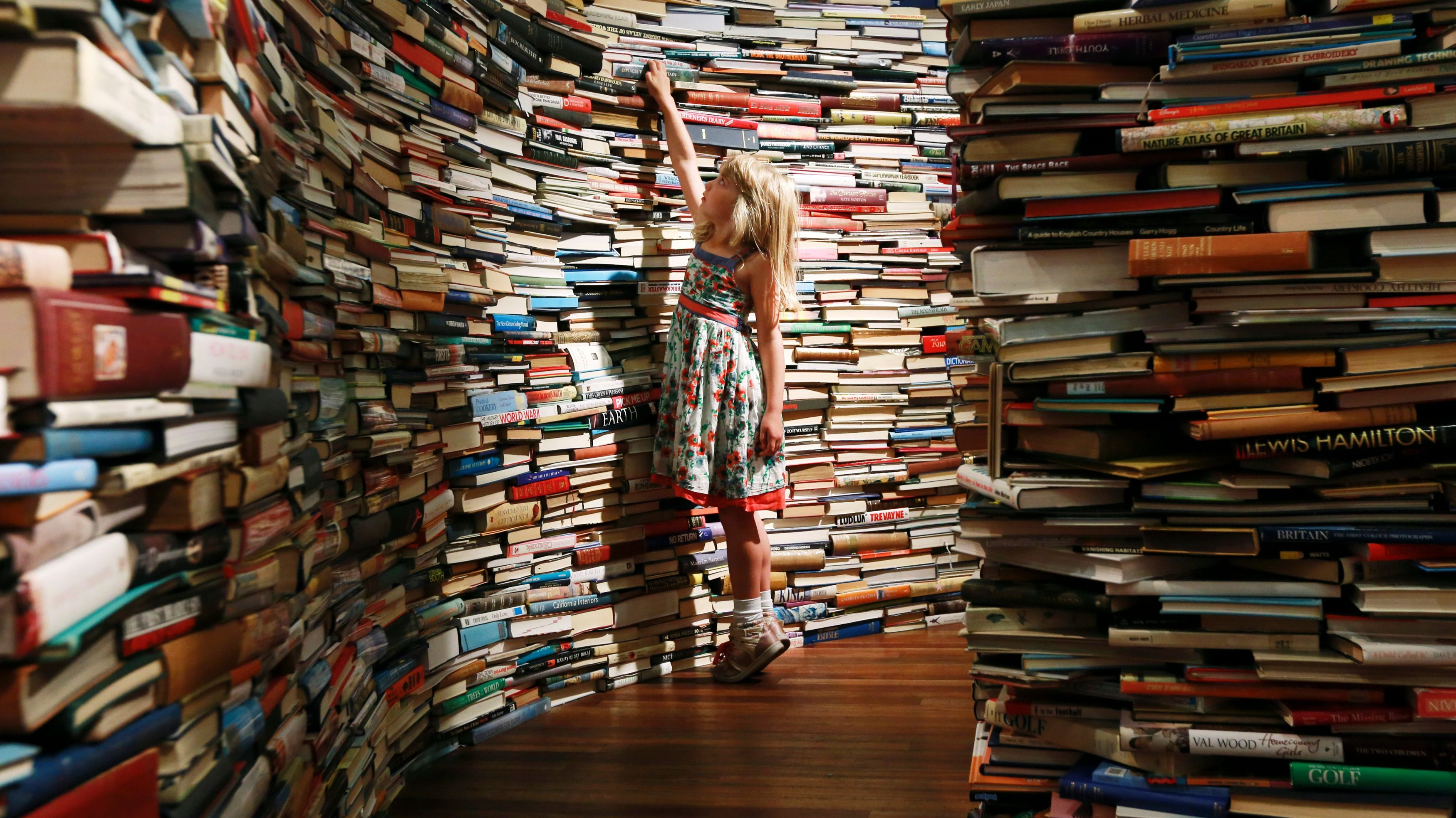 """Leona, 7, poses inside a labyrinth installation made up of 250,000 books titled """"aMAZEme"""" at the Royal Festival Hall in central London"""
