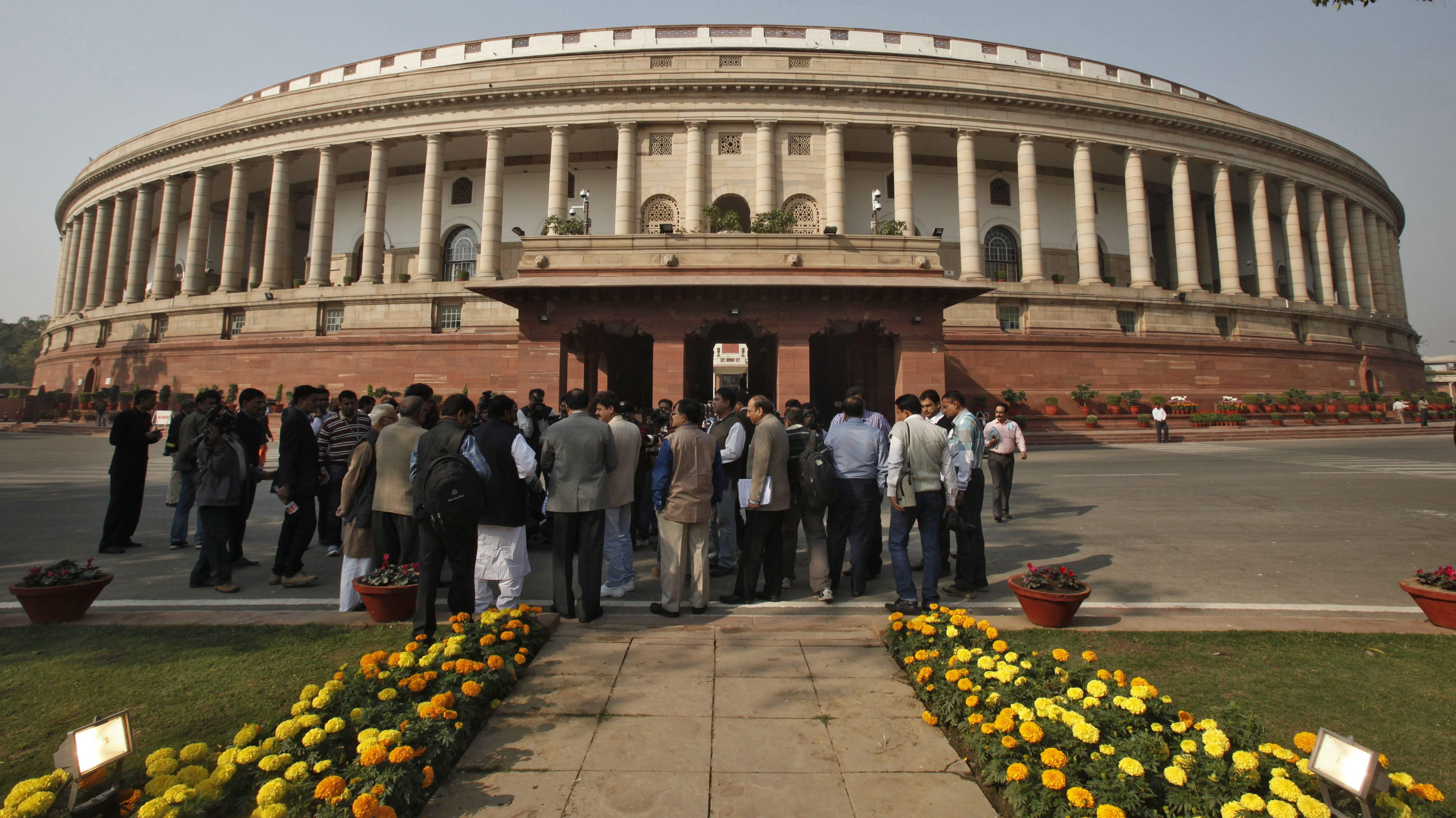 People stand in front of the Indian parliament building on the opening day of the winter session in New Delhi