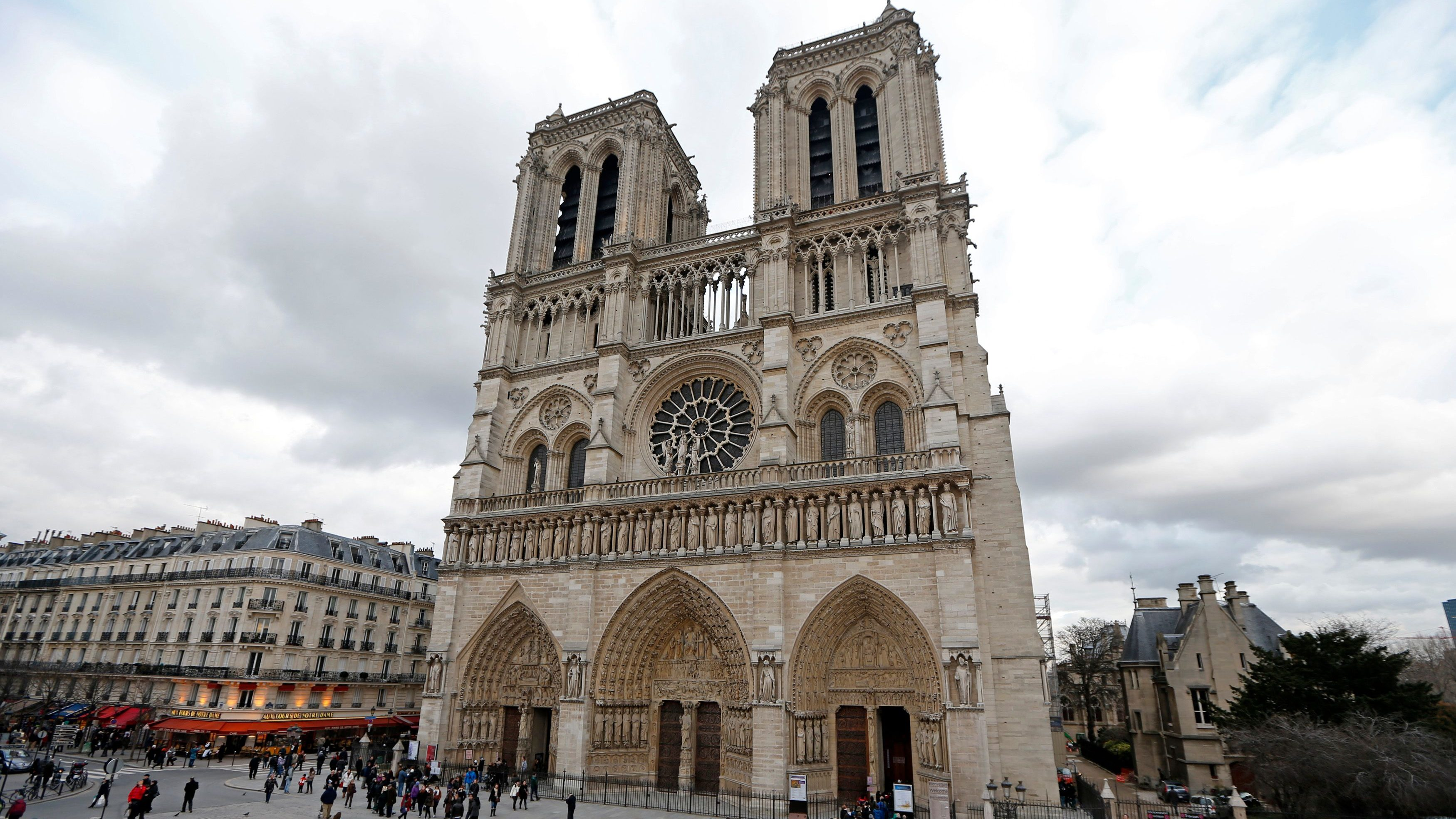 People walk past the entrance to the Notre Dame Cathedral in Paris