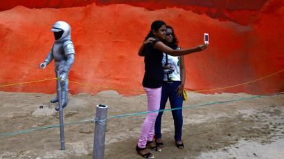 """Visitors take a selfie at a pandal, a temporary platform, with art installation titled """"Mars Mission"""" as part of the Durga Puja festival in Kolkata"""