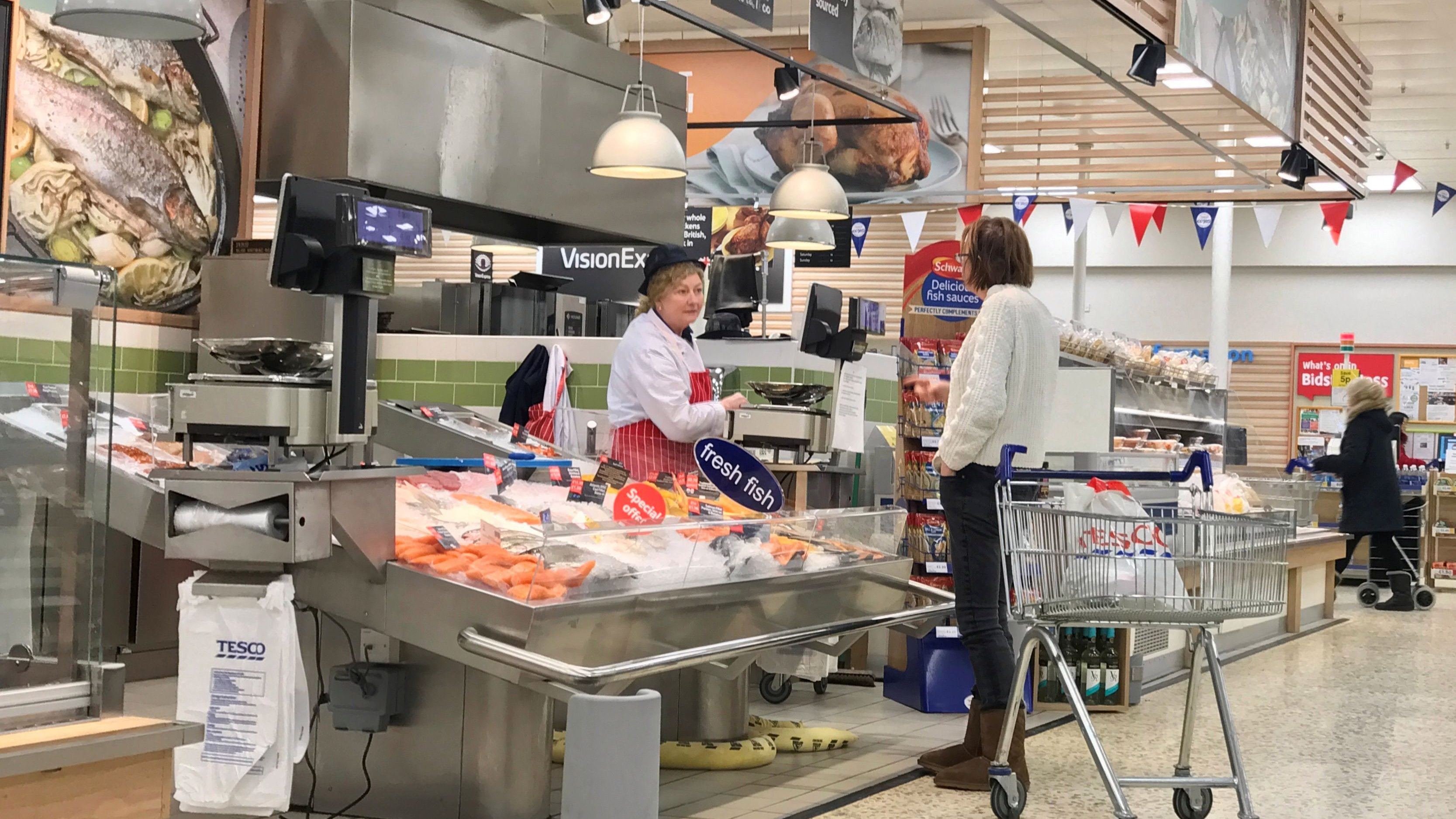 A customer talks to an in store fishmonger at a Tesco supermarket