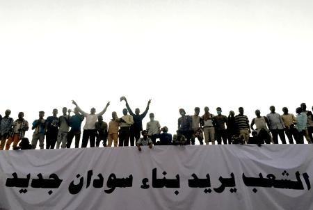 """Sudanese demonstrators stand next to a banner reading in Arabic """"People want to build new Sudan"""" as they chant slogans during a protest rally demanding Sudanese President Omar Al-Bashir to step down, outside Defence Ministry in Khartoum, Sudan April 9, 2019."""