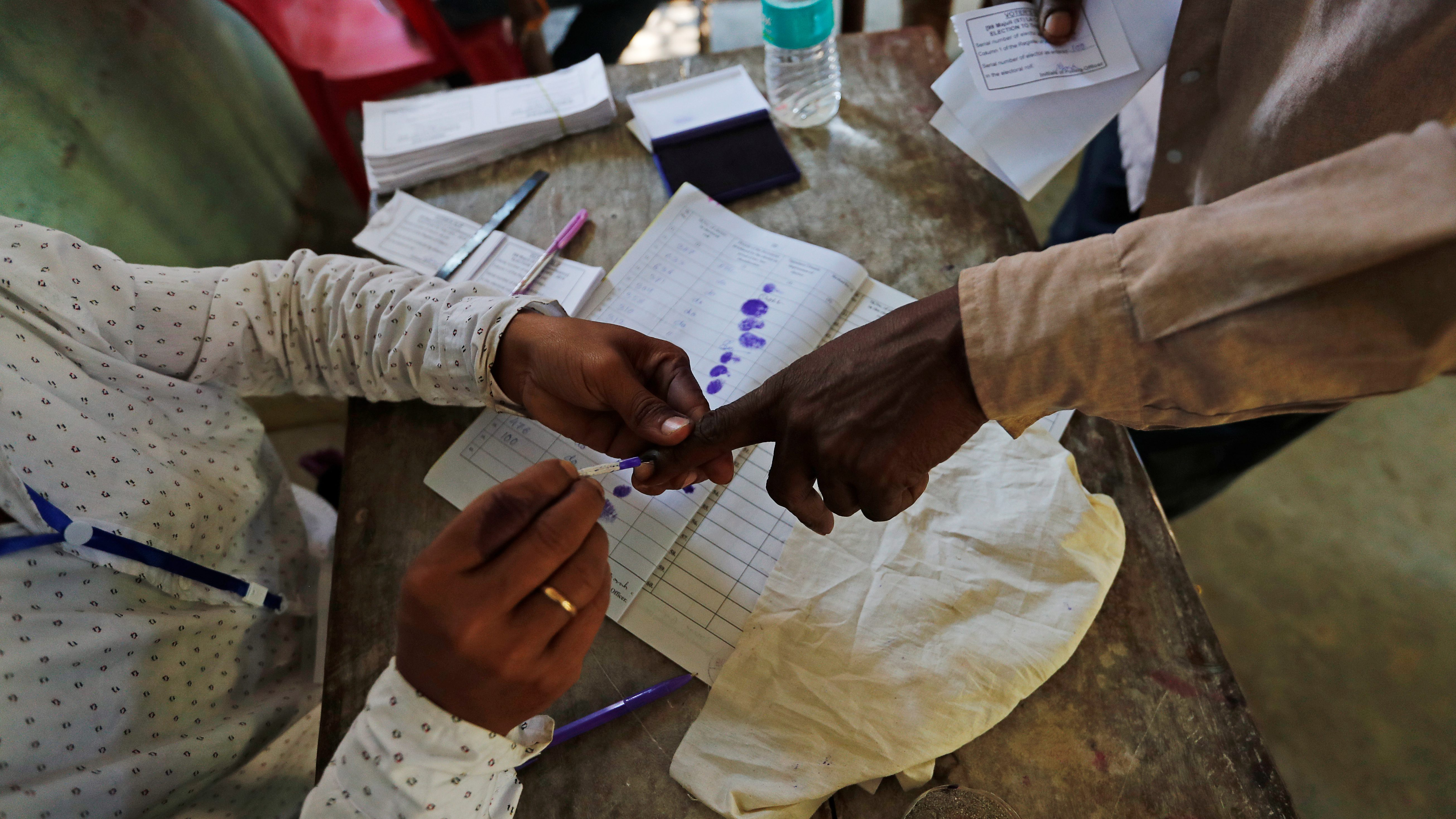 A man gets his finger inked before casting his vote at a polling station in Majuli