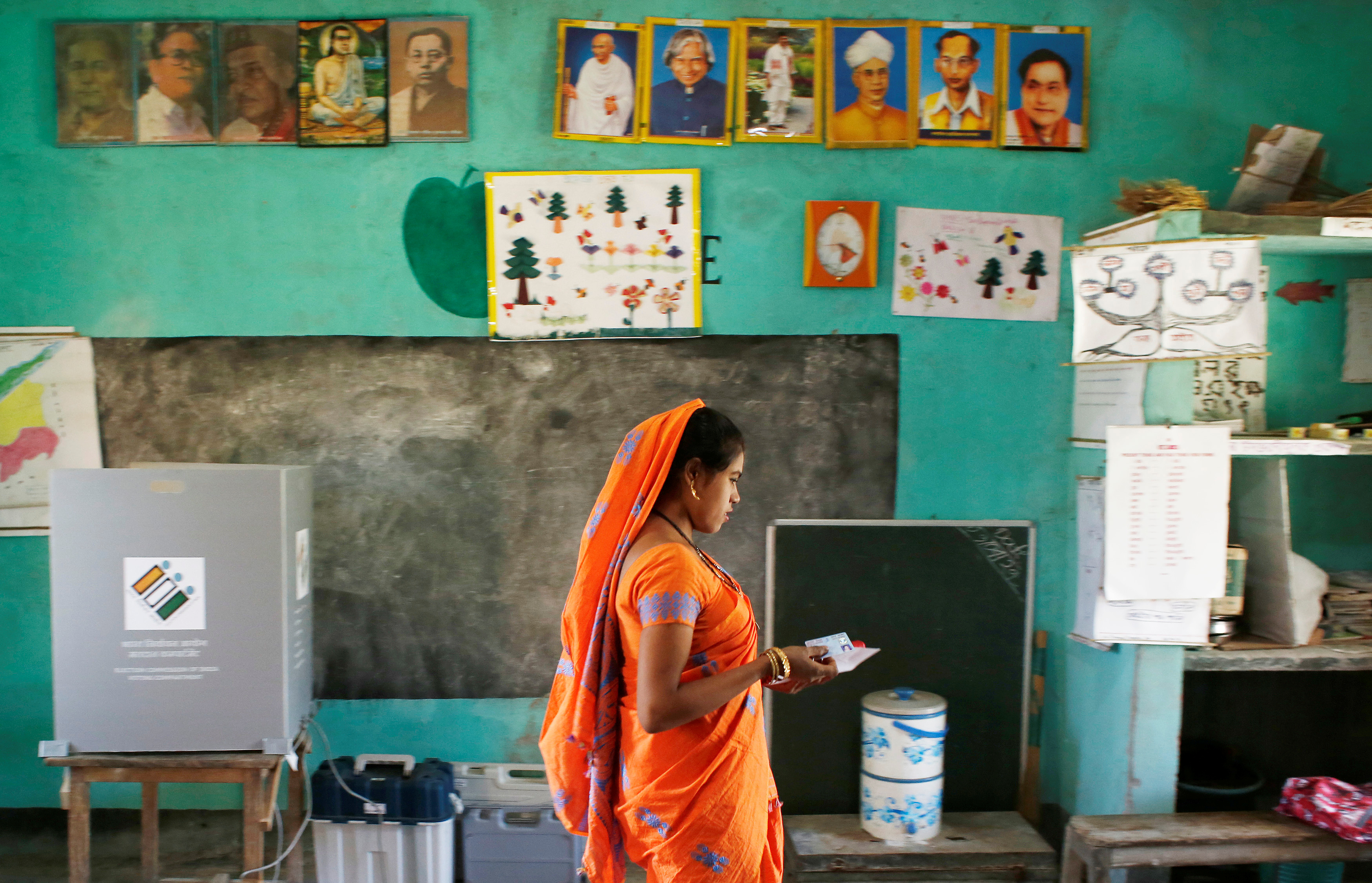 A woman leaves after casting her vote at a polling station during the first phase of general election in Majuli