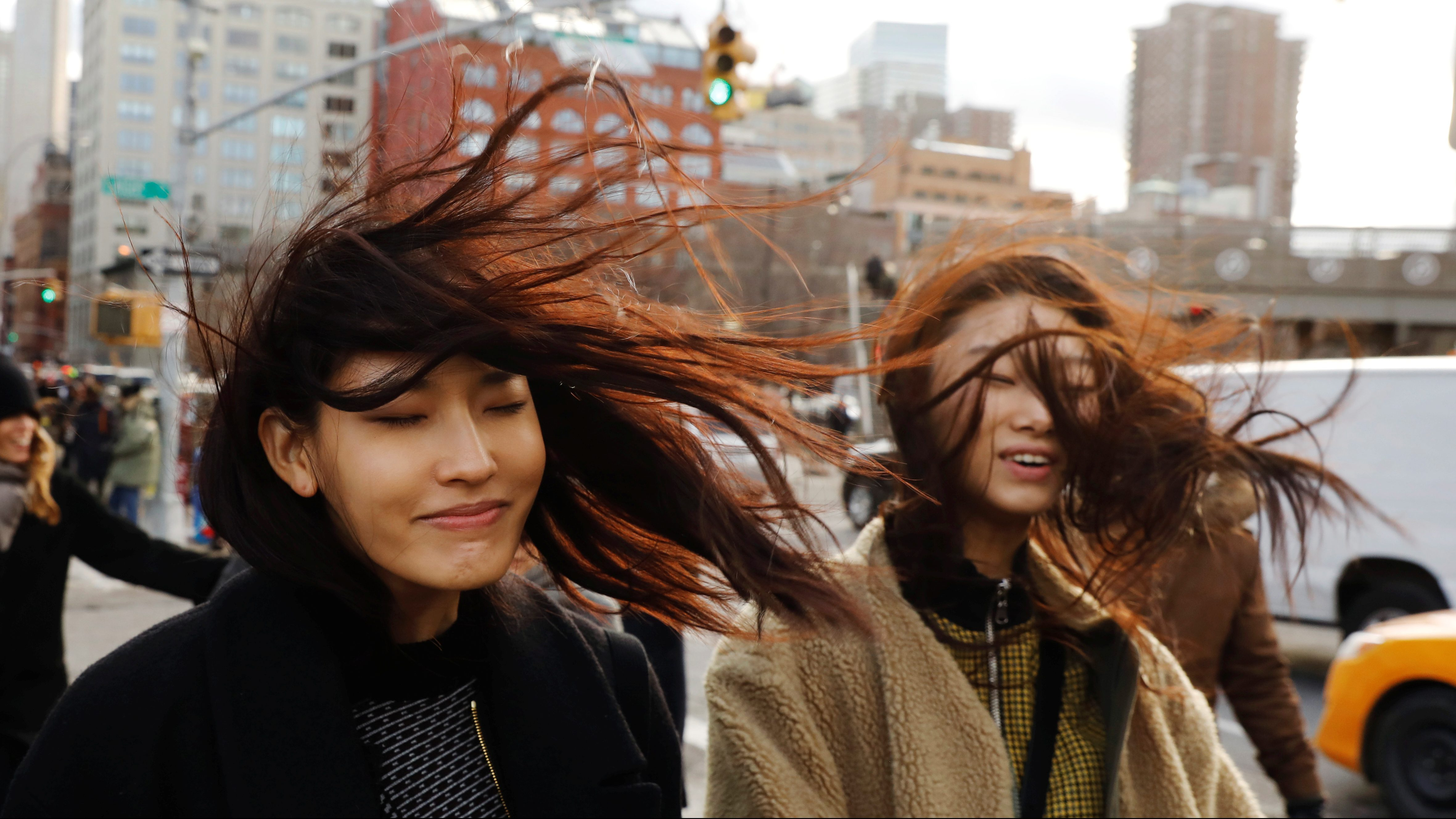 Two women react as the wind blows their hair around while walking on the street in the Manhattan borough of New York.